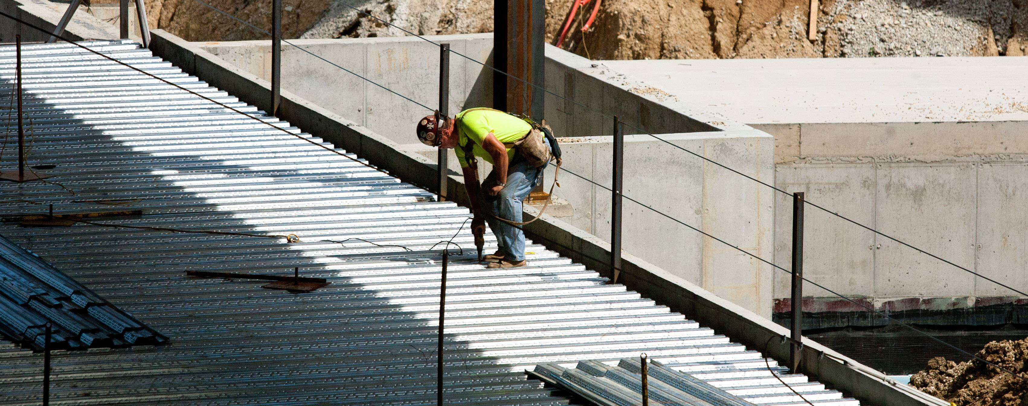 A construction worker secures decking material on Benedictine University's new College of Business building, which is scheduled for completion next summer.