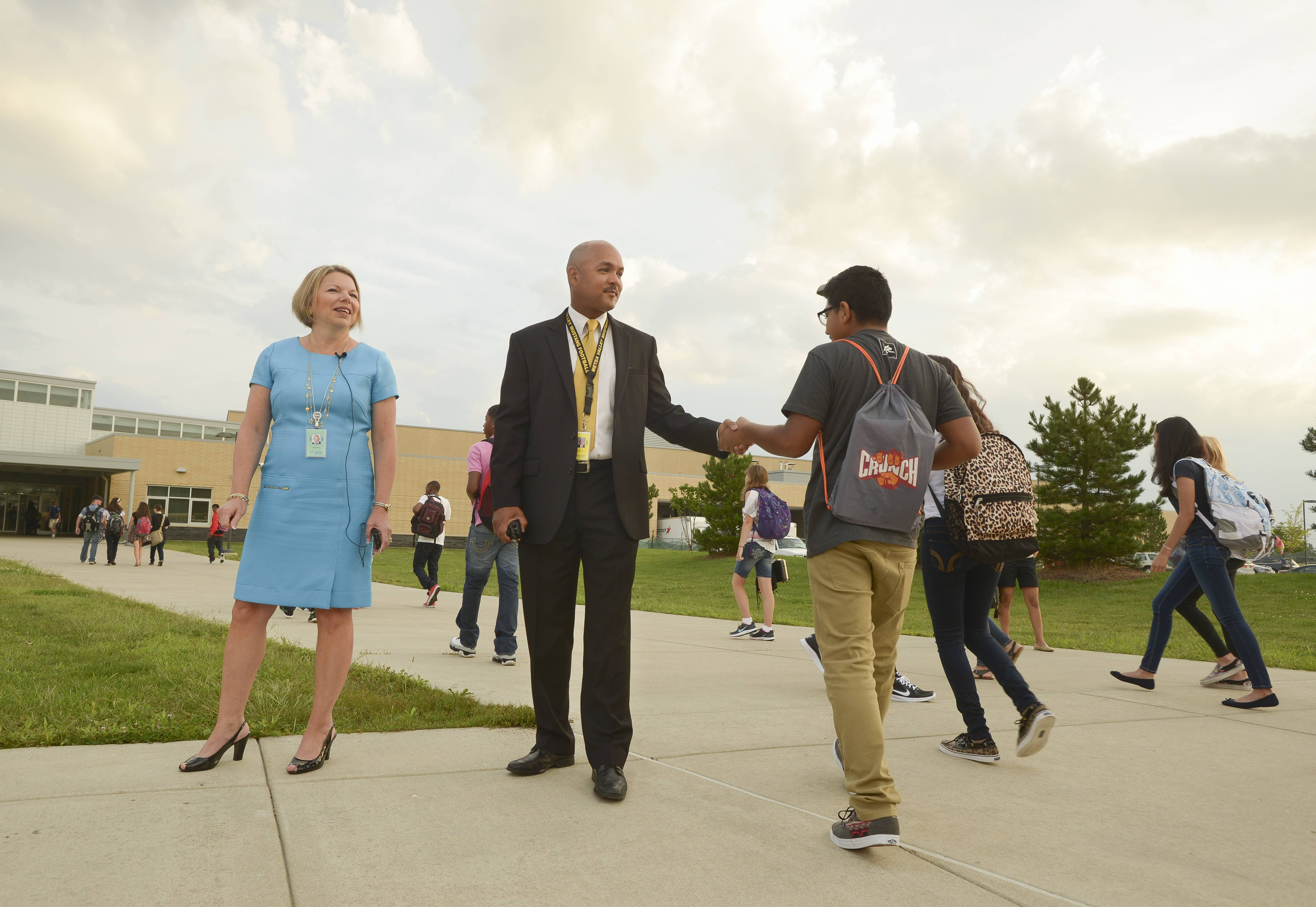 Karen Sullivan, the new superintendent of Indian Prairie Unit District 204, and Darrell Echols, new principal of Metea Valley High School, greet students as they arrive for the first day of classes at Metea Valley High School in Naperville.