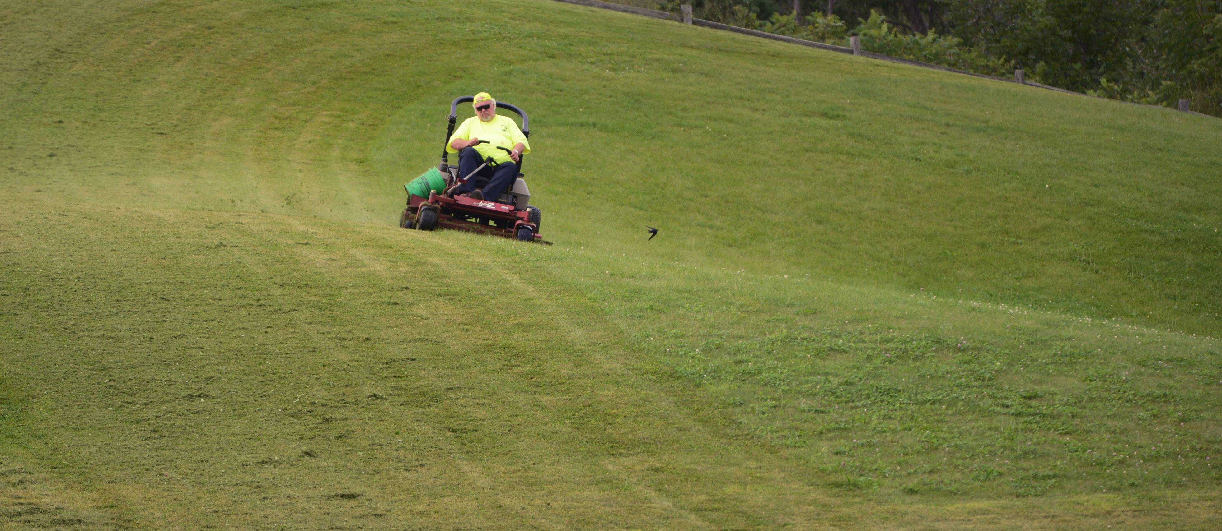 Island Lake Public Works crews cut the grass at Converse Park once a week. Worker Tom Benson hits the sledding hill as fellow workers cut the grass below.