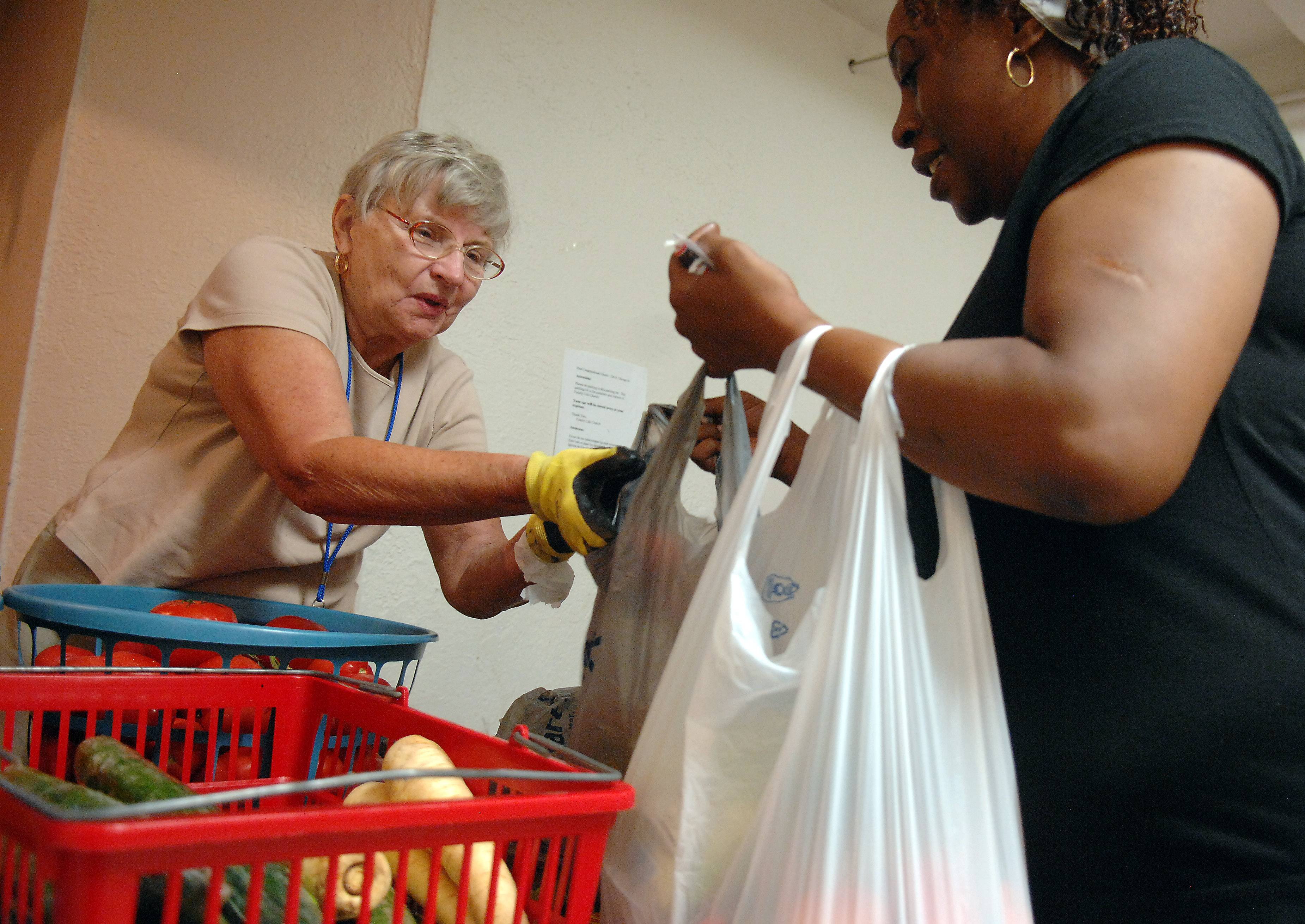 All Peoples Interfaith Food Pantry volunteer Lili Balasa, of Elgin, hands fresh produce to Shelley Hernandez of Elgin at the First Congregational Church in Elgin. Balasa has been a volunteer there for two years. The food pantry gets fresh produce twice a week from Jewel in South Elgin.