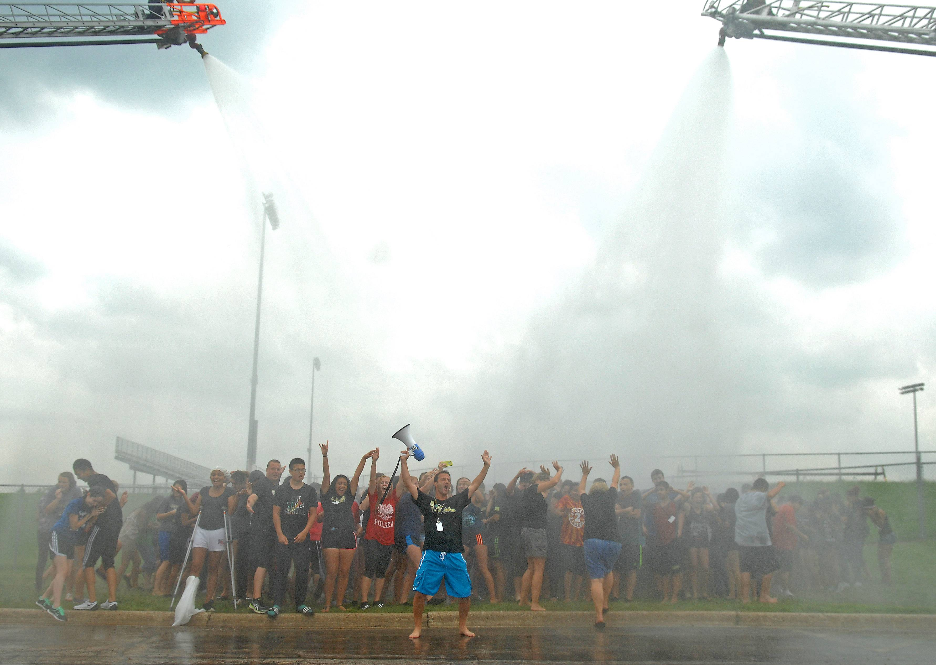About 400 Streamwood High School AVID students and teachers, including Mike Earone, with megaphone, are doused by Streamwood firefighters Friday as they accept the ALS Ice Bucket Challenge issued to them by Principal Terri Lozier. The students subsequently called out the football team to accept their ALS challenge. AVID (Advancement Via Individual Determination) is a college readiness program.