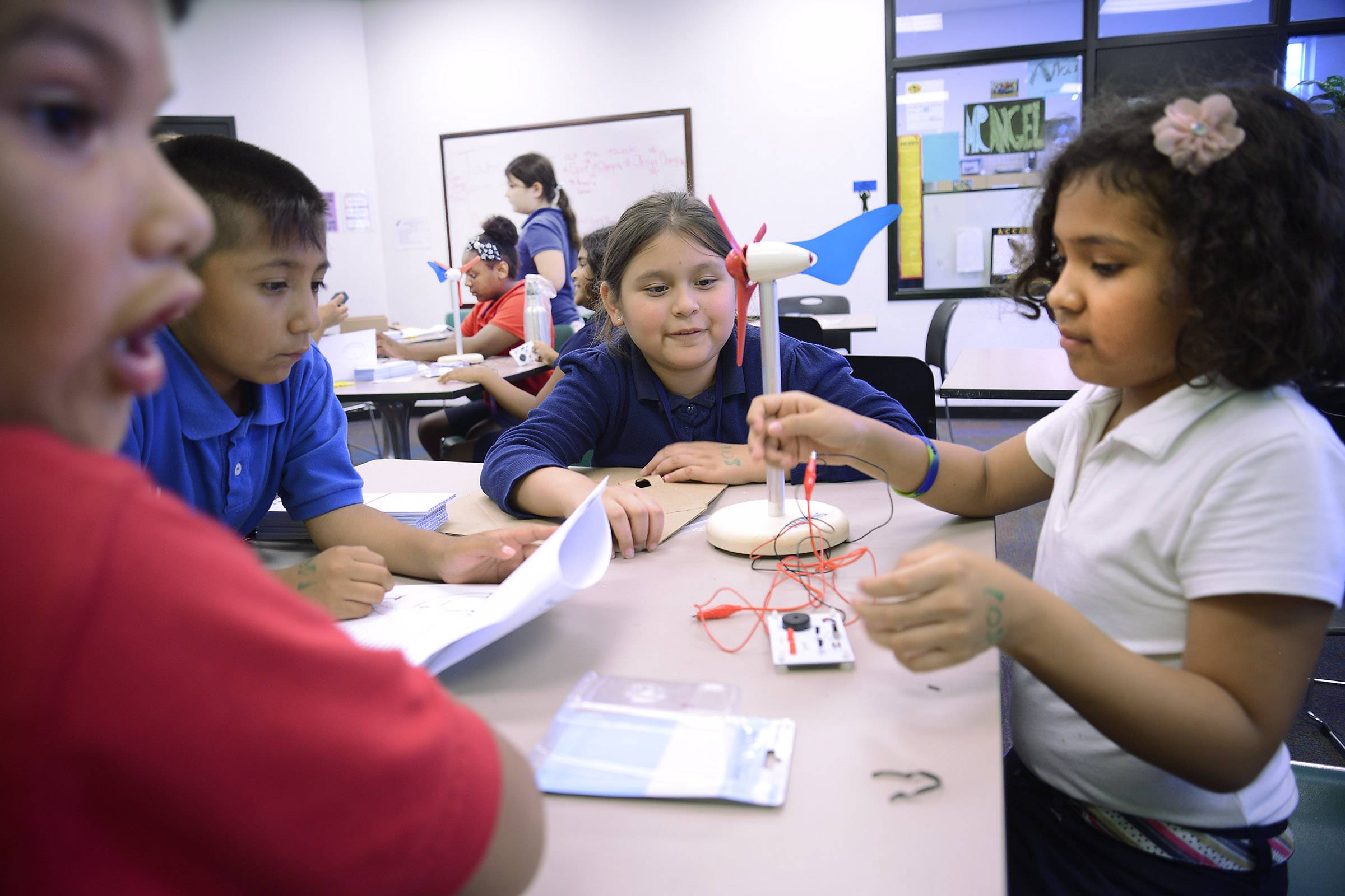 Oscar Jimenez, 9, left, Ryan Morales, 8, Coral Lopez, 8, and Dania Uribe, 8, right, work on their miniature wind turbine project at the Boys & Girls Club of Elgin Tuesday. Siemens USA brought their STEM (Science, Technology, Engineering and Math) program to the club and gave third and fourth graders the opportunity to build models of wind turbines as they learned about clean energy and possible careers in technology.