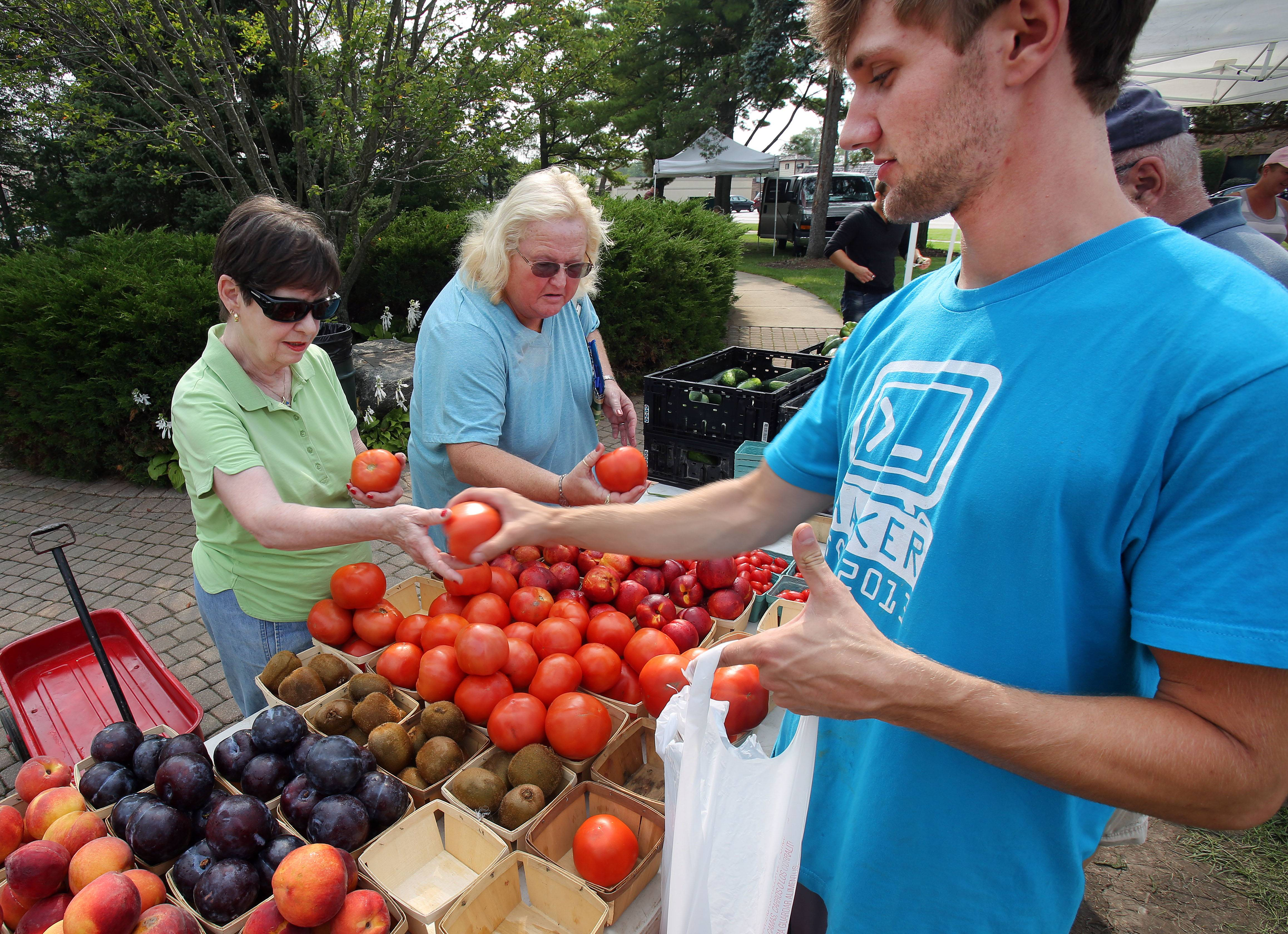 Susan McBride, left, of Lindenhurst, and Denise Christianson, of Waukegan, pick out tomatoes with help from Jared Jones, of Jerry Smith Pumpkin Farm in Kenosha, Wis., during the Gurnee farmers market at Esper Petersen Park Friday.
