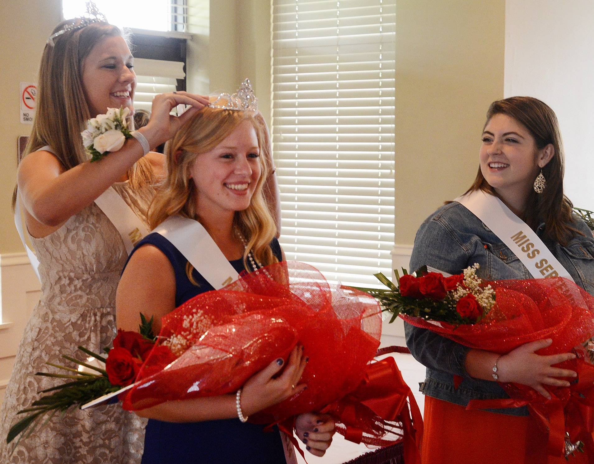 Carly Bryeans, 17, of Conant High School, is crowned Schaumburg's Miss Septemberfest 2014 by last year's Miss Septemberfest, Laura Sue Jensen, 19, of North Central College, Naperville. Runner-up Carolyn Byrne is on the right.