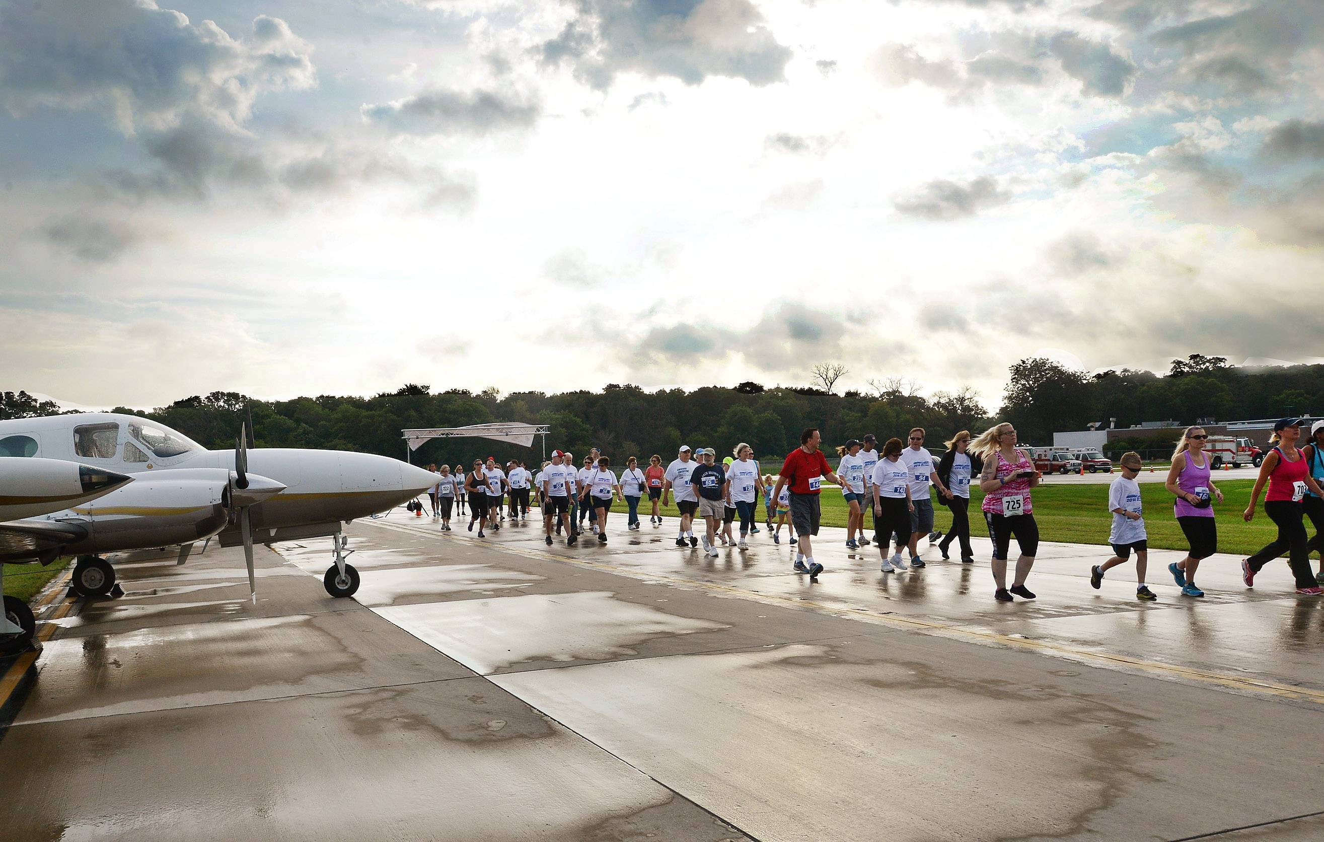 Runners take off down the runway for the Inaugural Run the Runway 5K Run &1 Mile Walk at Chicago Executive Airport in Wheeling.