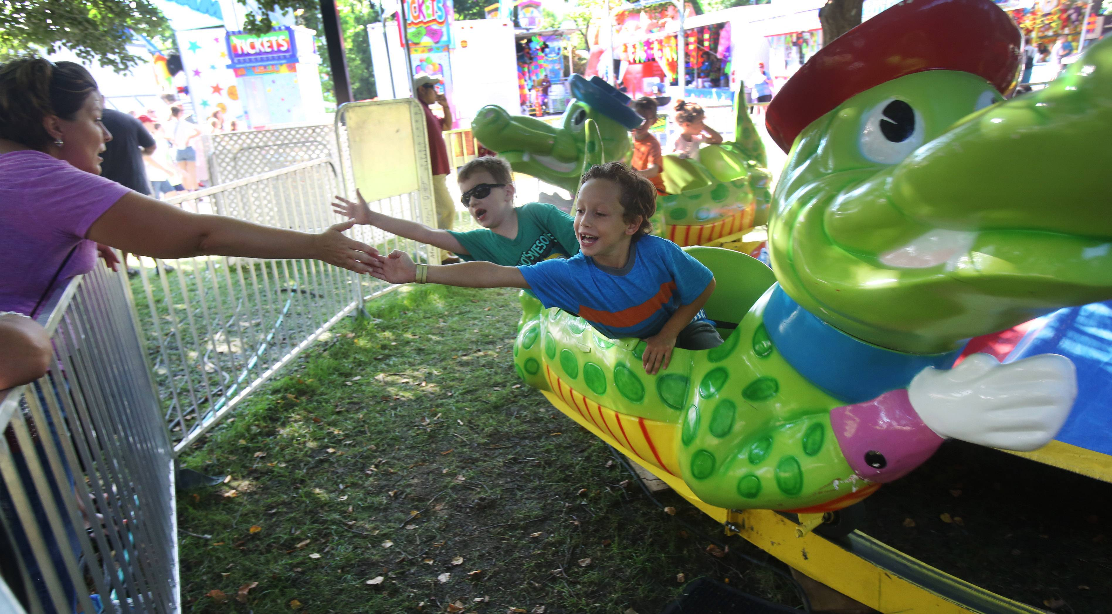 Seven-year-olds Domininc Samolinski, right, and Joe Stomiany, reach out to touch the hand of Melanie Gomez of Elk Grove Village on the Gator ride during Schaumburg's 44th Annual Septemberfest Sunday on the Schaumburg municipal grounds. The festival featured Brain Howe, lead singer of the band Bad Company, and fireworks later in the evening..