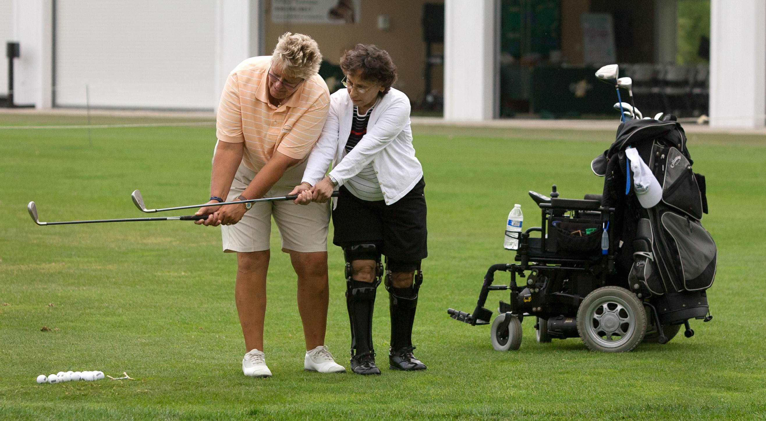 Kathy Williams, left, of Revelation Golf, teaches club speed to Judi Ruiz as part of a monthly golf clinic at Cantigny Golf, in Wheaton, for veterans with physical disabilities and PTSD syndrome.