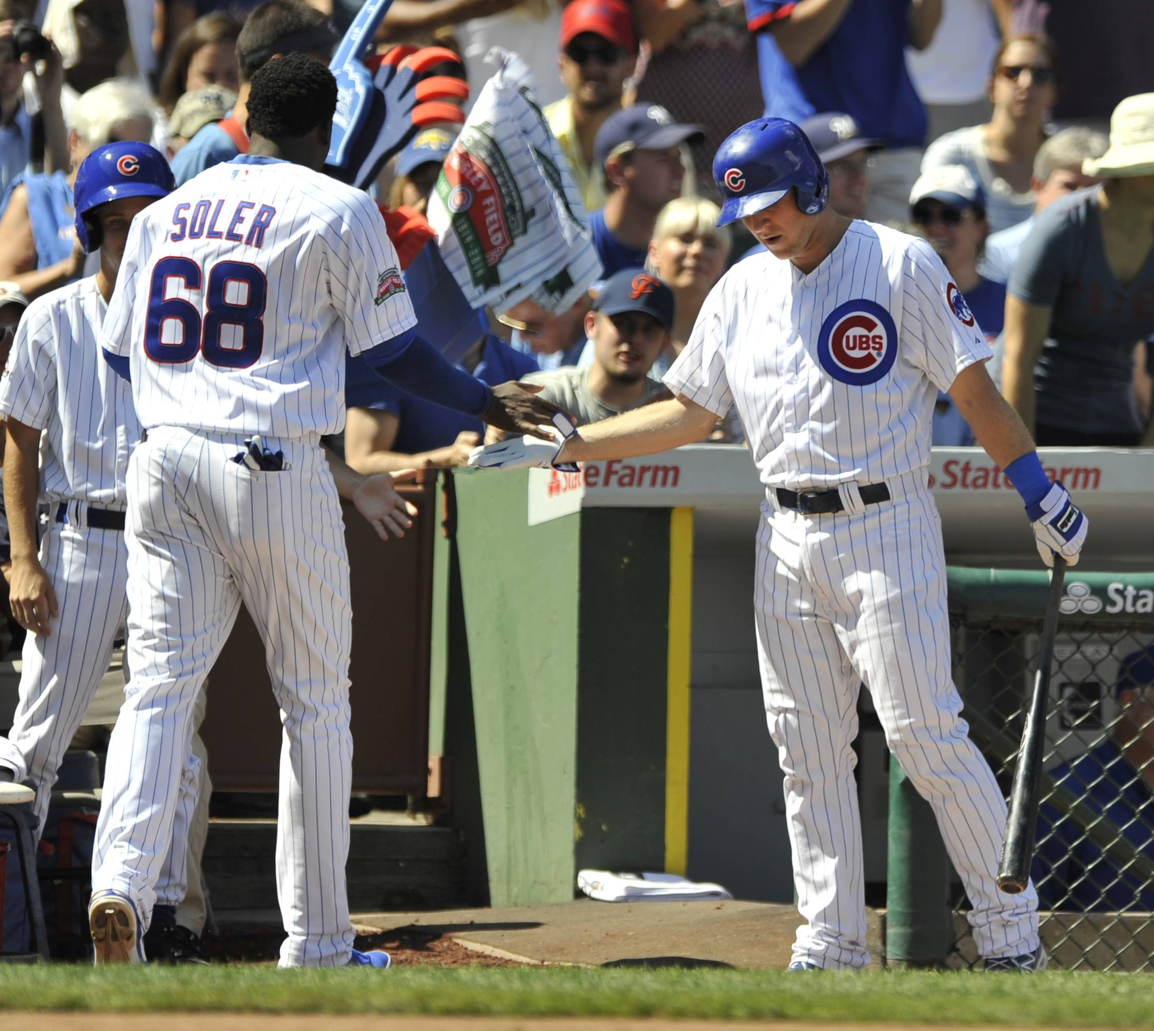 Cubs slugger Jorge Soler (68) celebrates with teammate Chris Valaika, right, after scoring on a Welington Castillo single during the second inning of a baseball game against the Milwaukee Brewers in Chicago, Monday, Sept. 1, 2014.