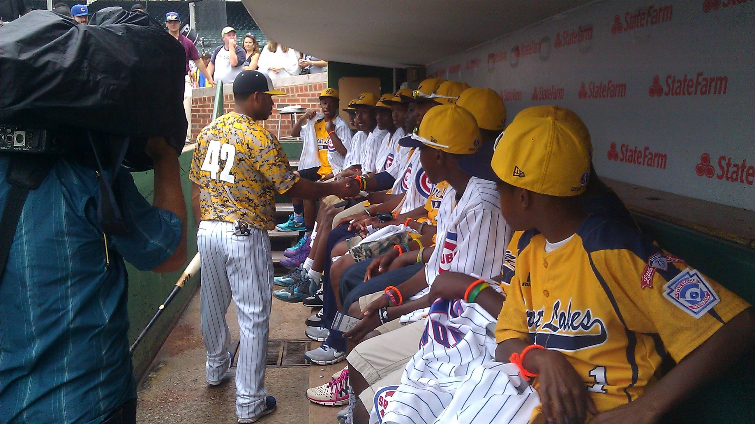 Cubs third baseman Luis Valbuena greets members of the Jackie Robinson West Little League team. Cubs players wore special warm-up jerseys before Monday's game against the Milwaukee Brewers. The jerseys honored JRW and featured the No. 42 in honor of Jackie Robinson.
