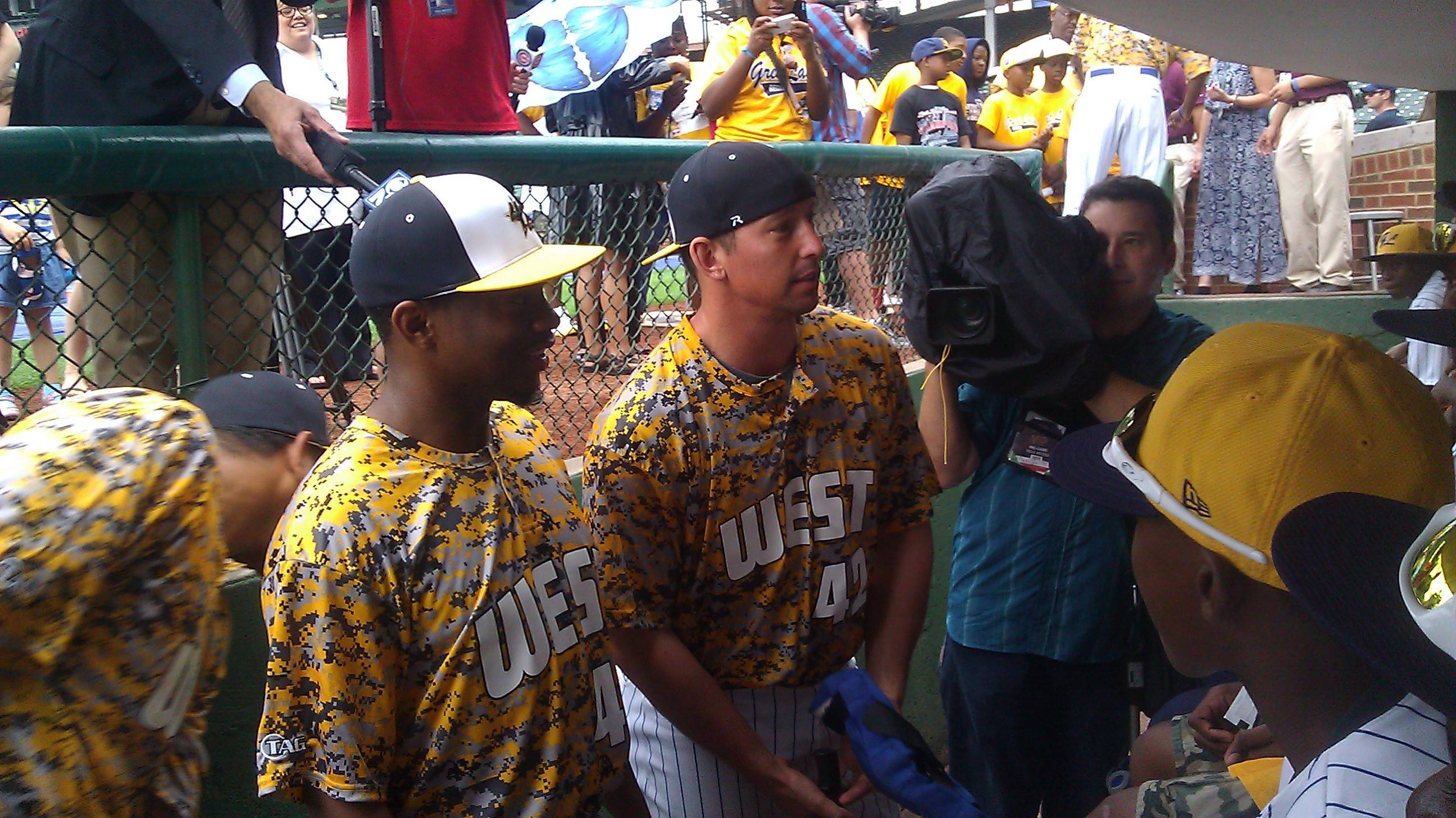Cubs pitcher Wesley Wright, left, and catcher John Baker talk with members of the Jackie Robinson West Little League team Monday in the dugout at Wrigley Field. Cubs players wore special warm-up jerseys to honor the United States championship team.