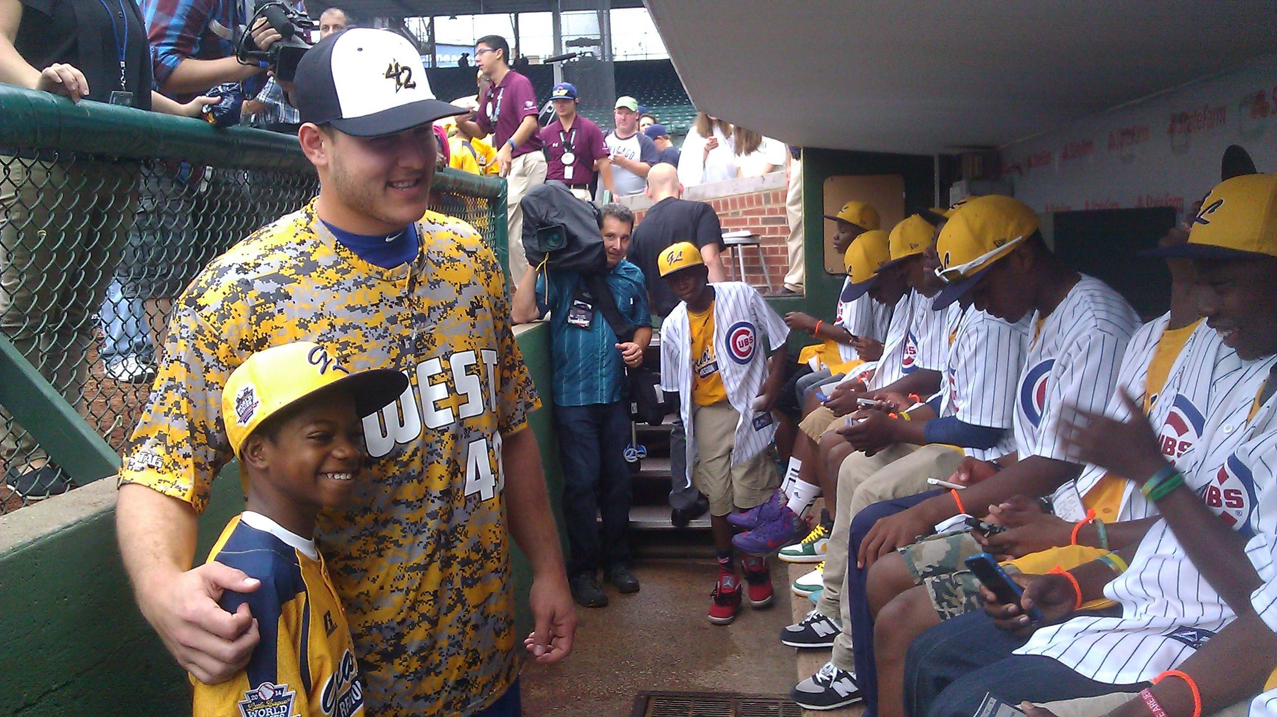 Cubs first baseman Anthony Rizzo visits in the dugout Monday at Wrigley Field with members of the Jackie Robinson West Little League national champions.