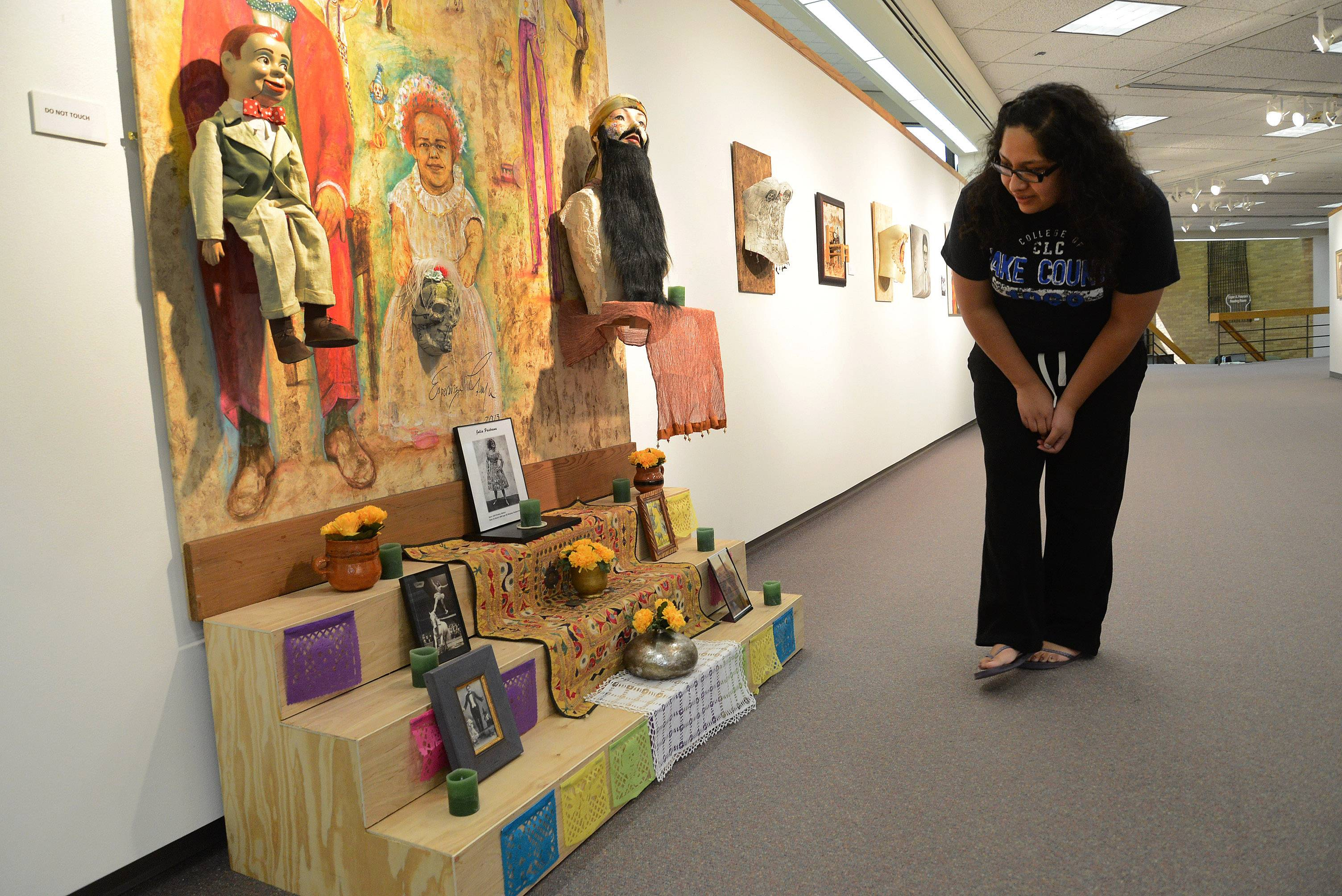 "College of Lake County student Nancy Antonio of Waukegan, gets a close look at ""The Day of the Dead Dedicated to Julia Pastrana,"" from the ""Esperanza Gama: A Series of Memories"" exhibit at the College of Lake County's Robert T. Wright Gallery in Grayslake."