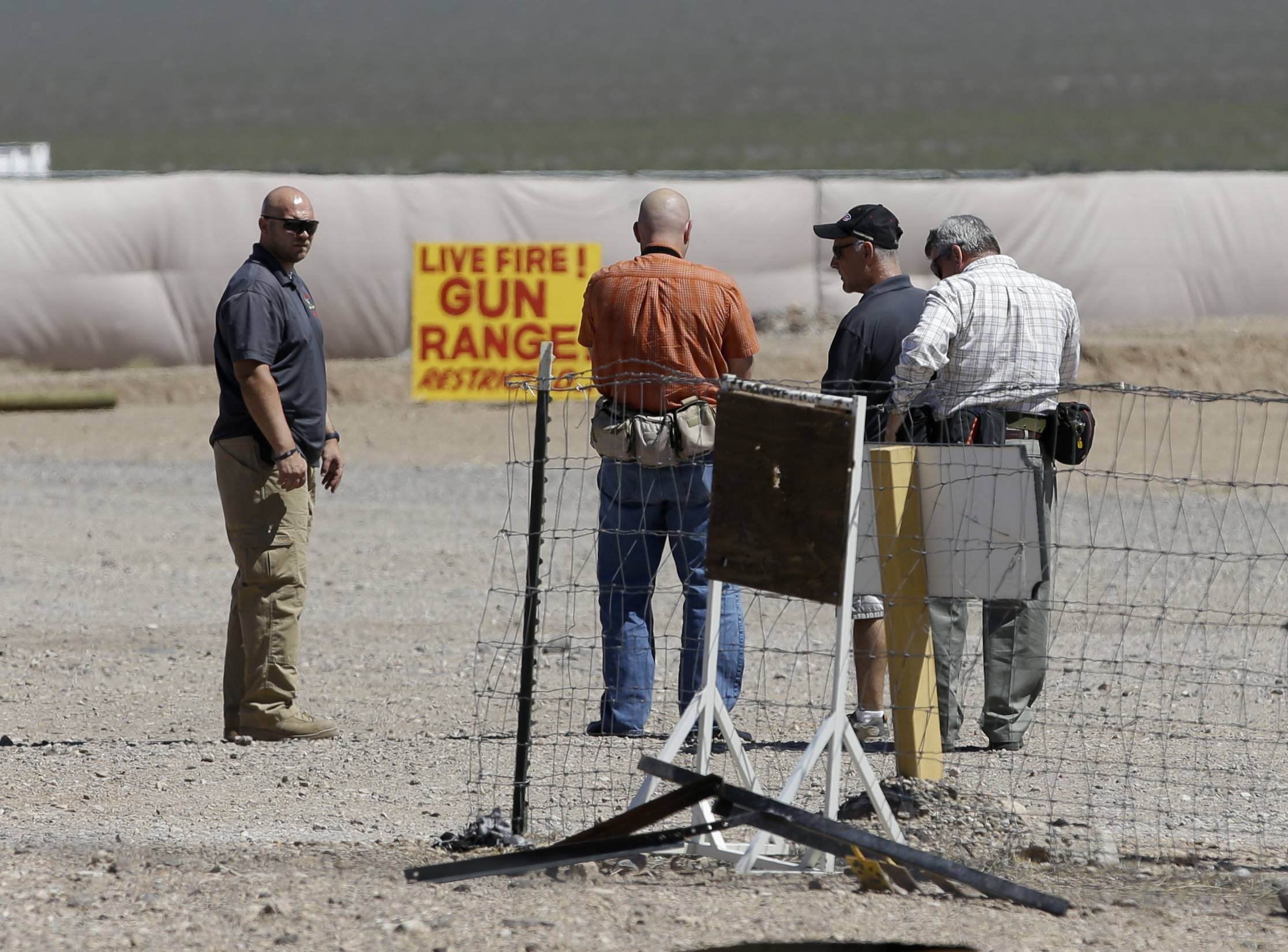 People are seen at the Last Stop outdoor shooting range Wednesday, Aug. 27, 2014, in White Hills, Ariz. Gun range instructor Charles Vacca was accidentally killed Monday, Aug. 25, 2014 at the range by a 9-year-old with an Uzi submachine gun.