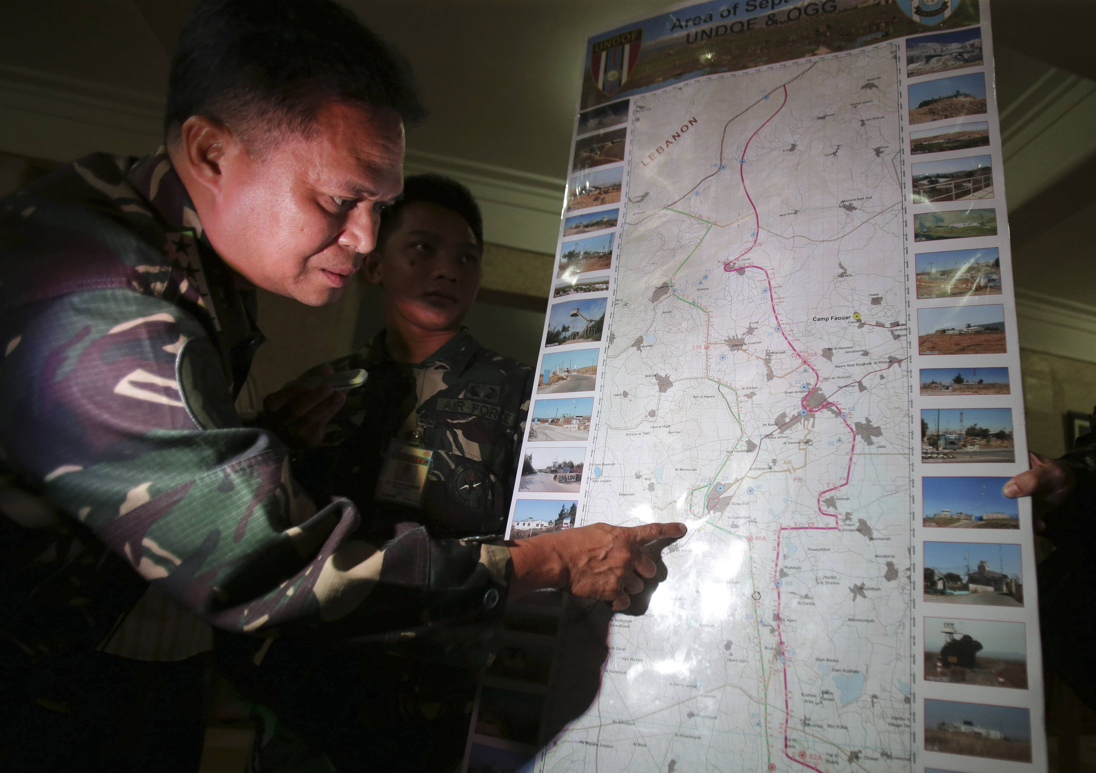 Philippine military chief Gen. Gregorio Pio Catapang shows reporters where Filipino peacekeepers in Golan Heights have been repositioned during a press conference at Camp Aguinaldo military headquarters in suburban Quezon city, Philippines on Sunday Aug. 31, 2014. Catapang said more than 70 Filipino peacekeepers have escaped from two areas in the Golan Heights that came under attack by Syrian rebels.