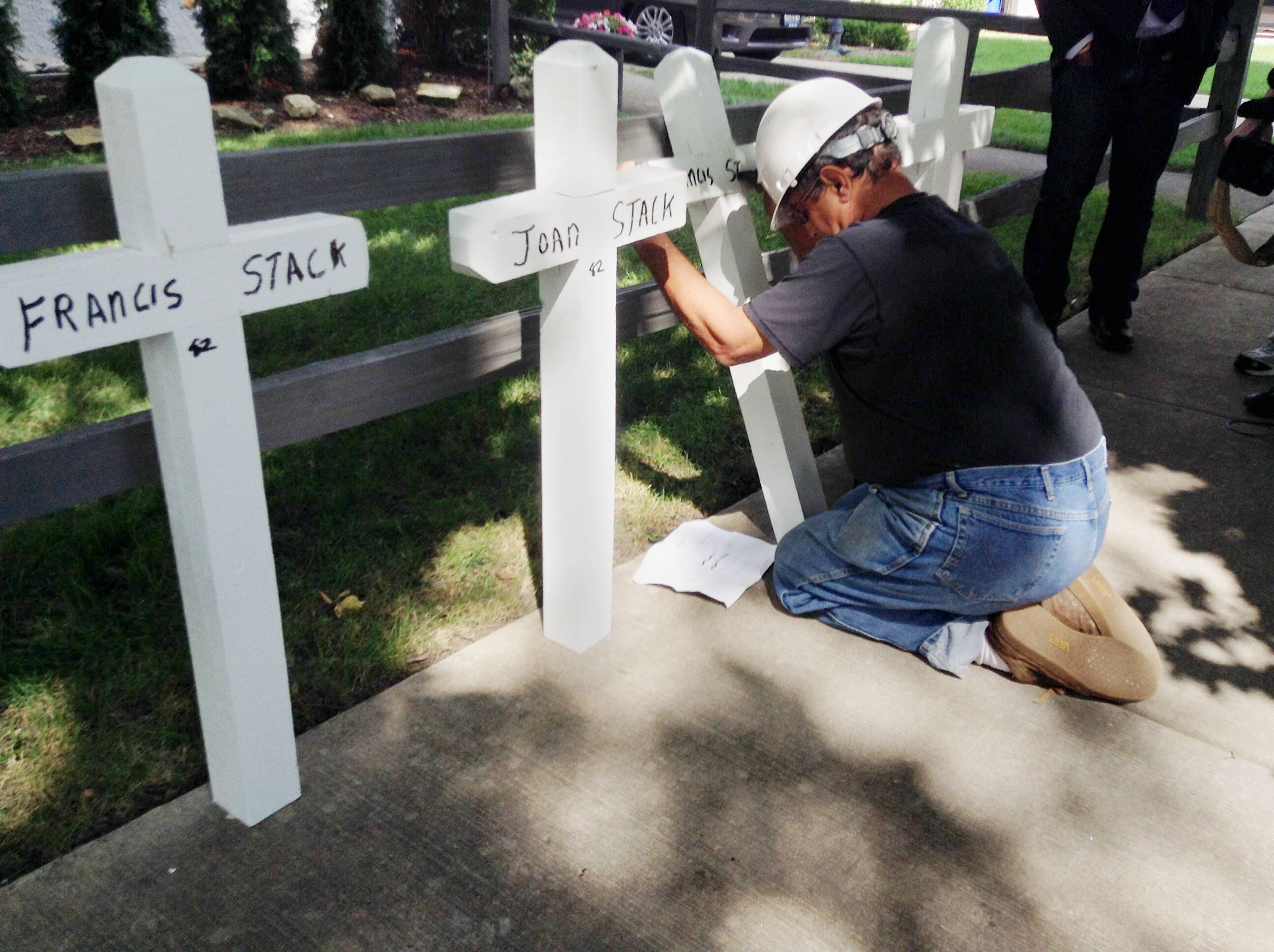 Greg Zanis of Aurora places white crosses with the names of the four members of Stack family outside the family's Elmhurst home Sunday morning. Francis, Joan, Mary and Francis Stack Jr. died in what police are calling a triple murder and suicide.