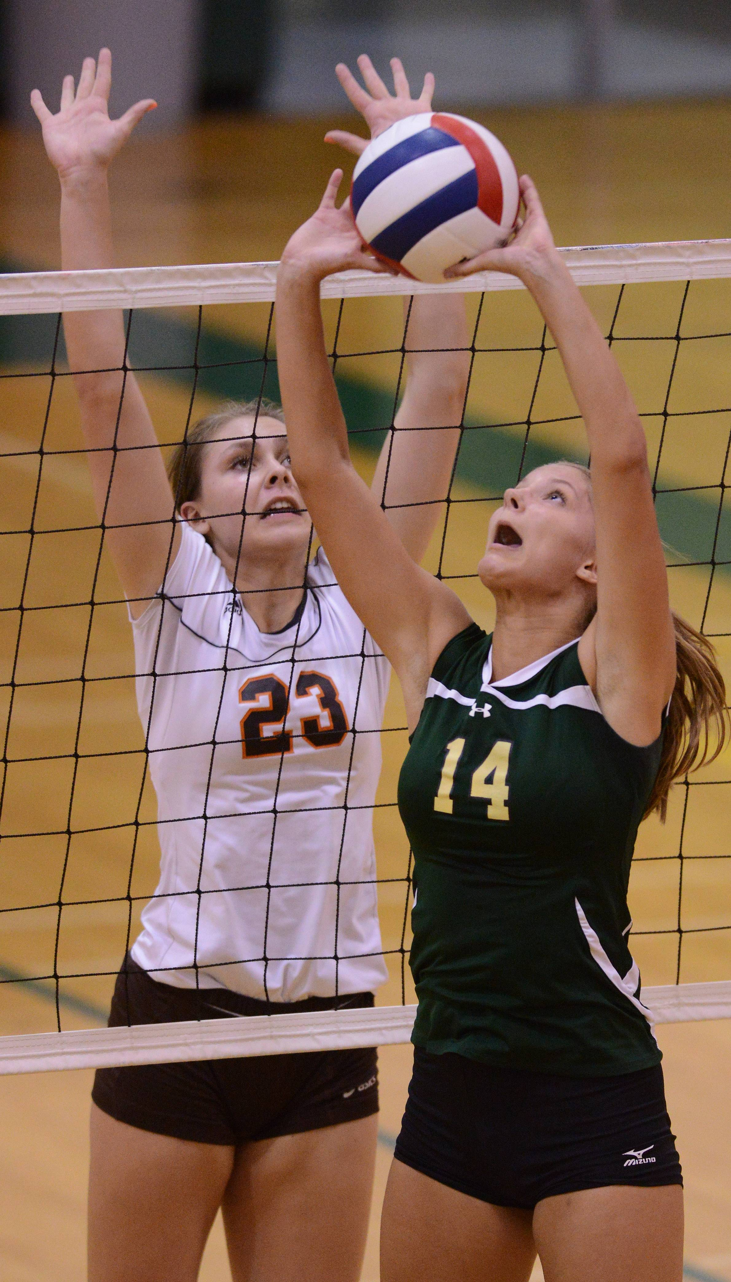 Fremd's Carly Roberts sets the ball at the net in front of Hersey's Liz Fuerst during Tuesday's volleyball match at Fremd in Palatine.