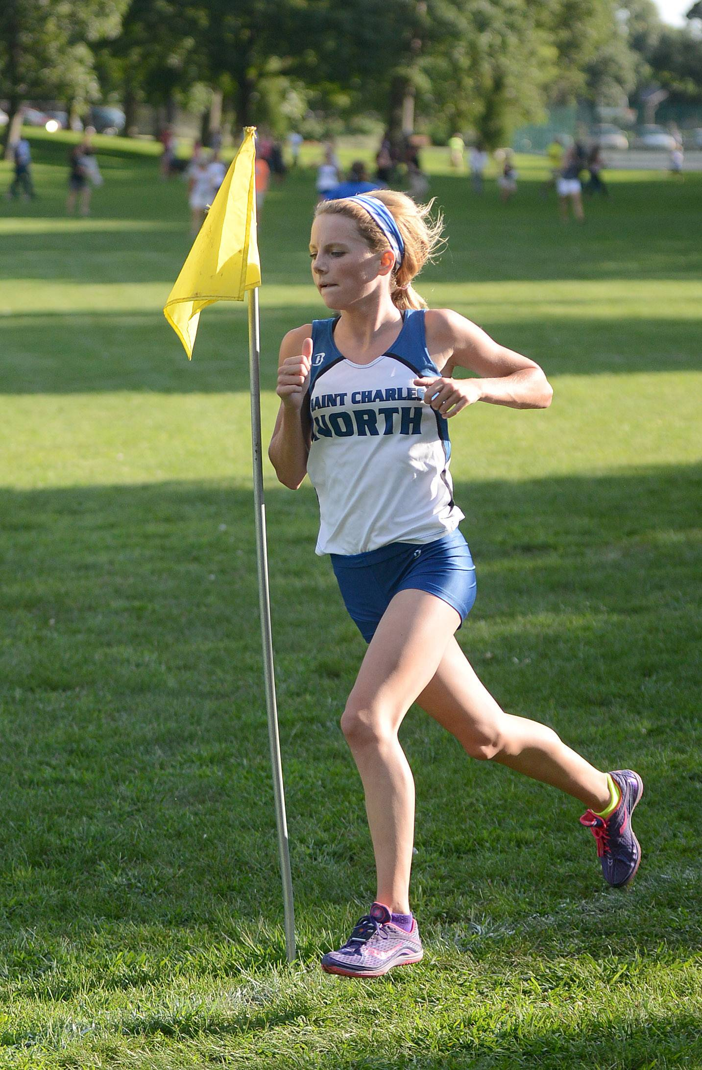 St. Charles North's Audrey Ernst leads and wins the girls varsity run at the Elgin Invite cross country meet at Lords Park in Elgin on Tuesday.