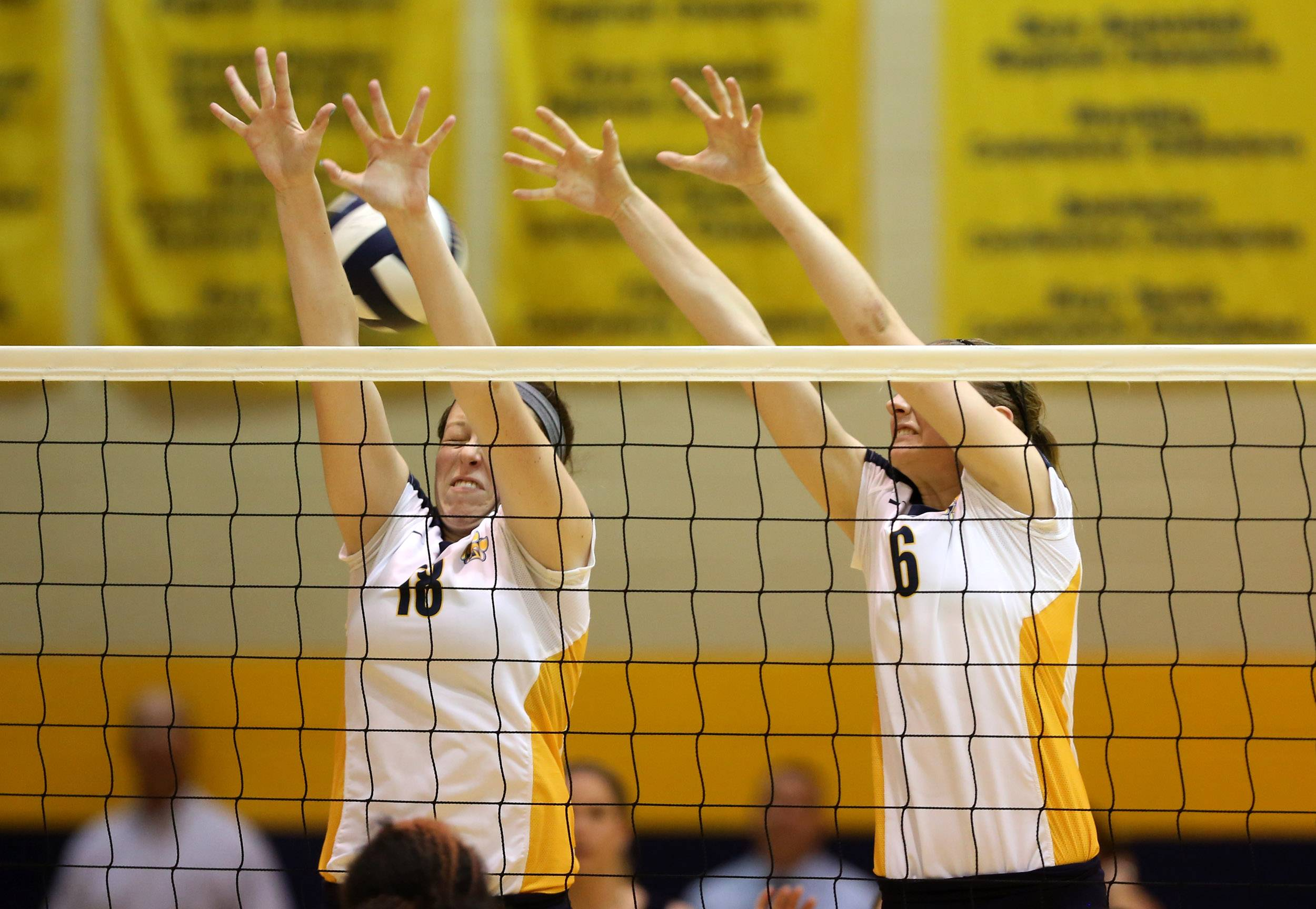Neuqua Valley's Kaelan Haag, left, and Anne Botos, right, attempt to defend a Metea Valley spike during girls volleyball action in Naperville.
