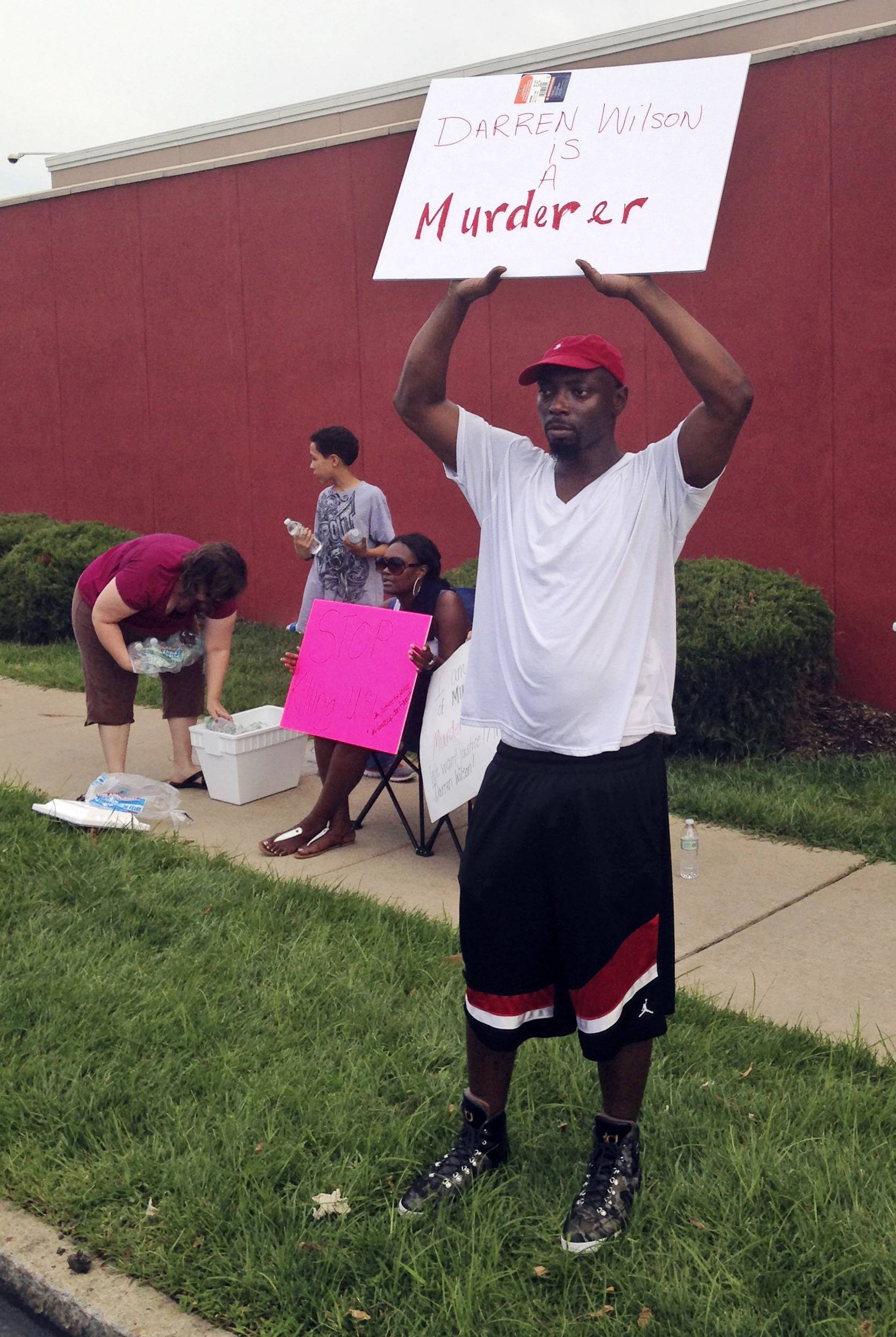 "Lamont Jones holds up a sign reading ""Darren Wilson is a Murderer,"" in St. Louis. Jones was reacting to a rally supporting Wilson, the white officer who shot unarmed, black 18-year-old Michael Brown in Ferguson, Mo. Like many Americans, Jones has formed concrete opinions about the case."