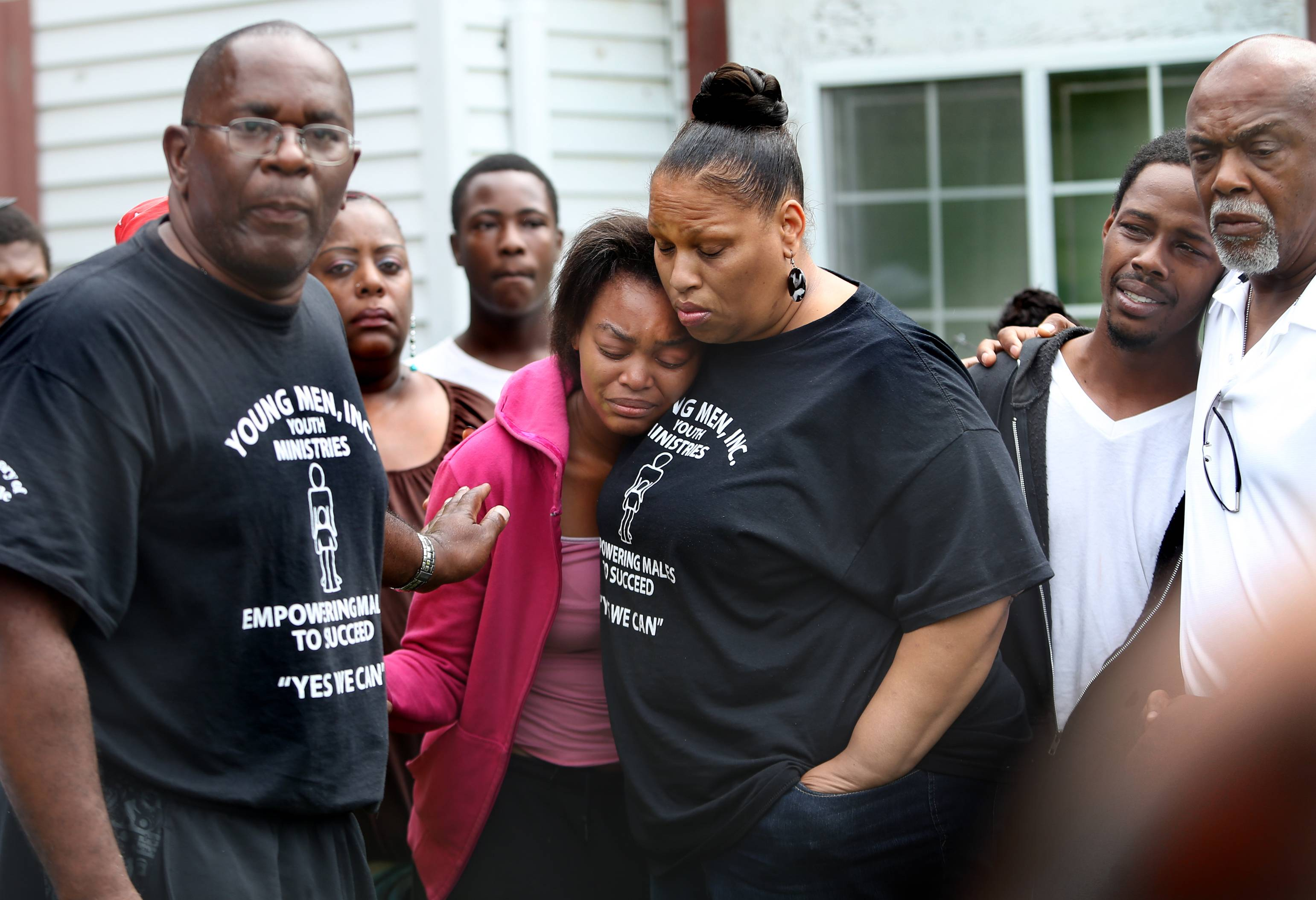 Taniasha Perkins, center, and Willie Wilson, second from right, are comforted as Rev. Malachi Walker, left, makes a plea for the return of the couple's missing 6-week-old son, Delano Wilson.