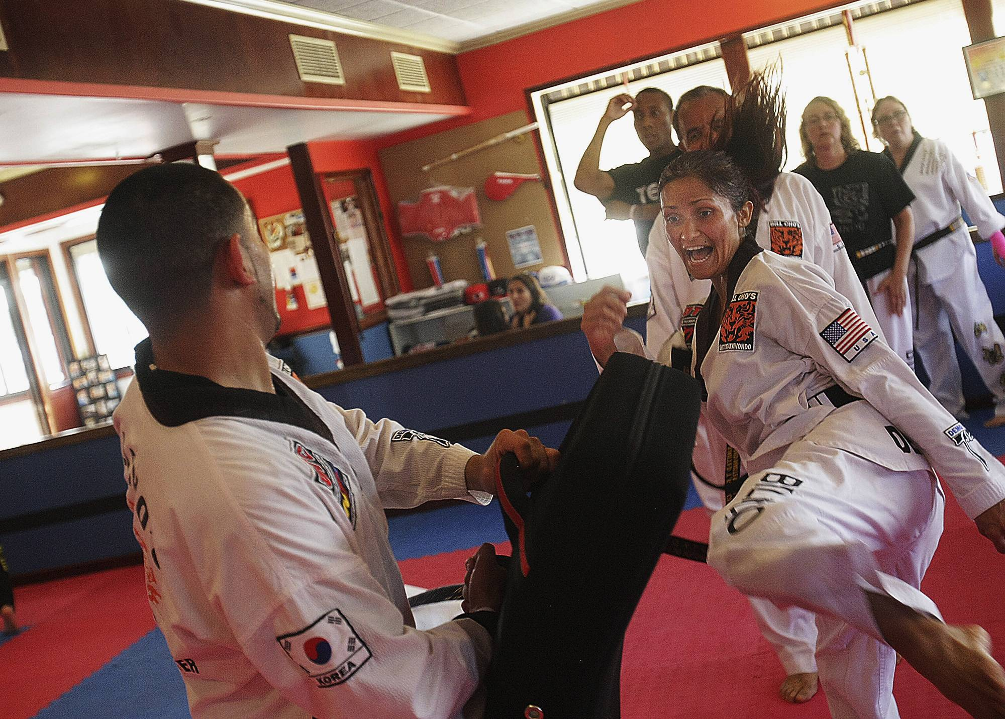 Katherine Hryniewicki, right, of Sycamore,  kicks a bag held by Victor Perez during a class at Bill Cho's United Taekwondo Center in Sycamore.