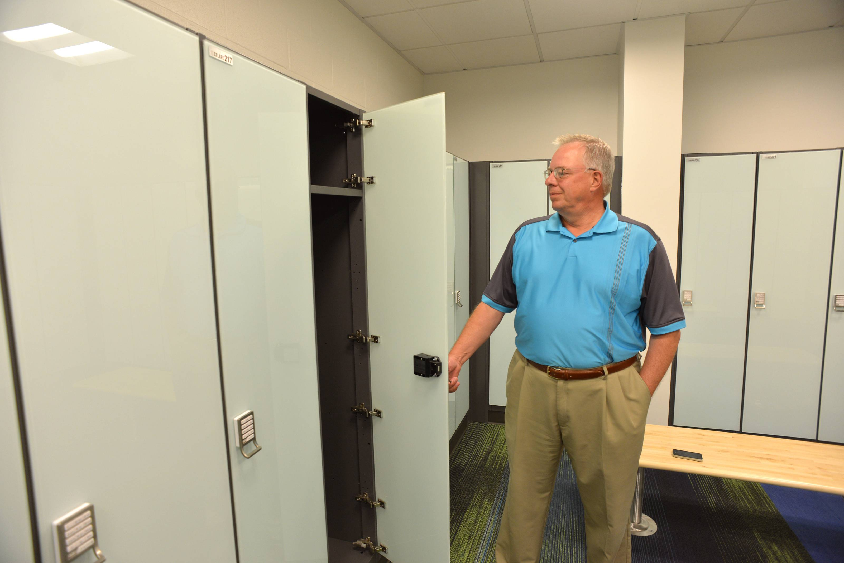West Chicago Park District Executive Director Gary Major shows off the tempered glass fronts on lockers in the new ARC Center.