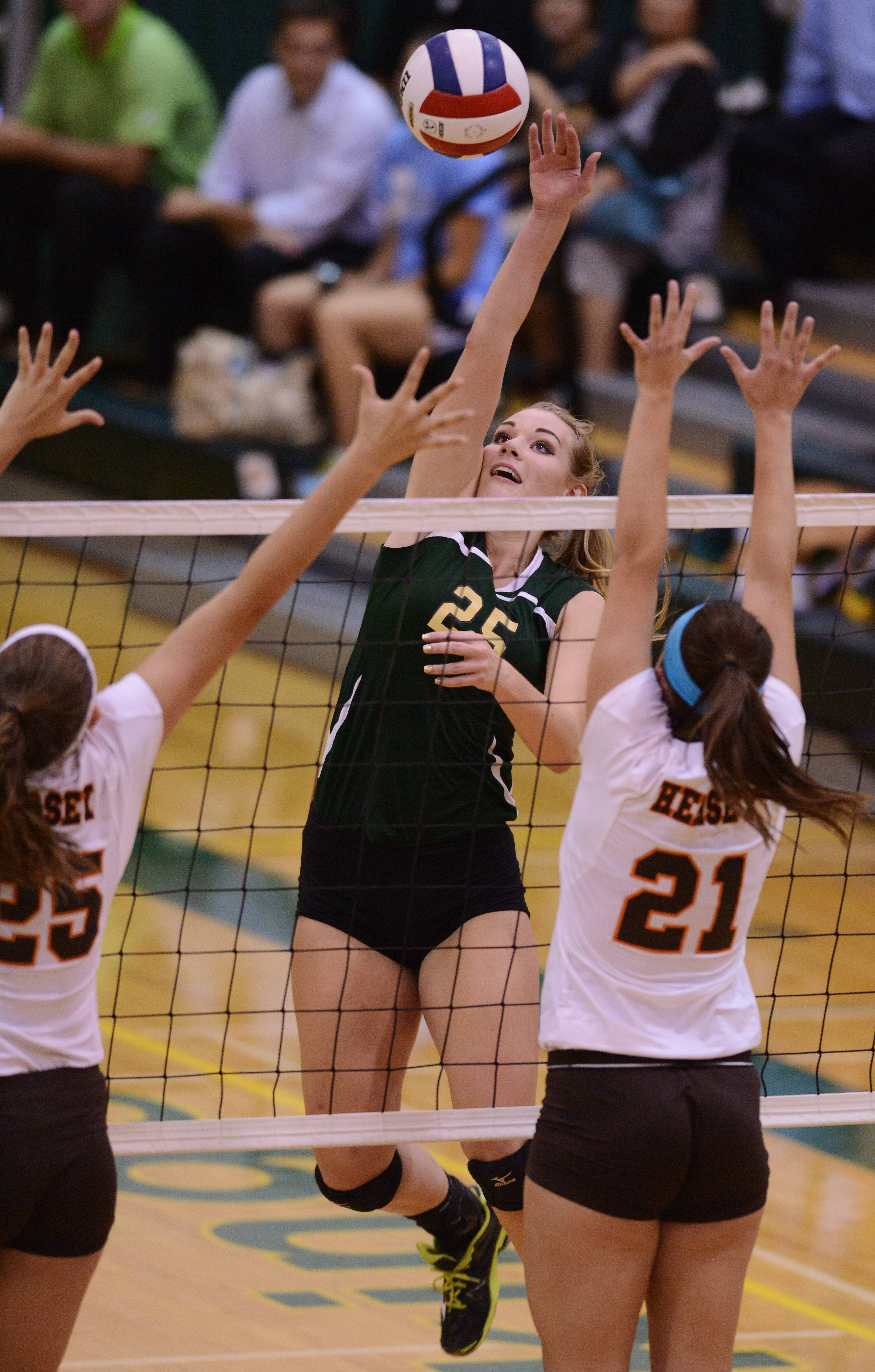 Fremd's Lane Hindenburg leaps for a kill as Hersey's Gabrielle Olhava, left, and Courtney Stedman try to block the ball at the net during Tuesday's volleyball match in Palatine.