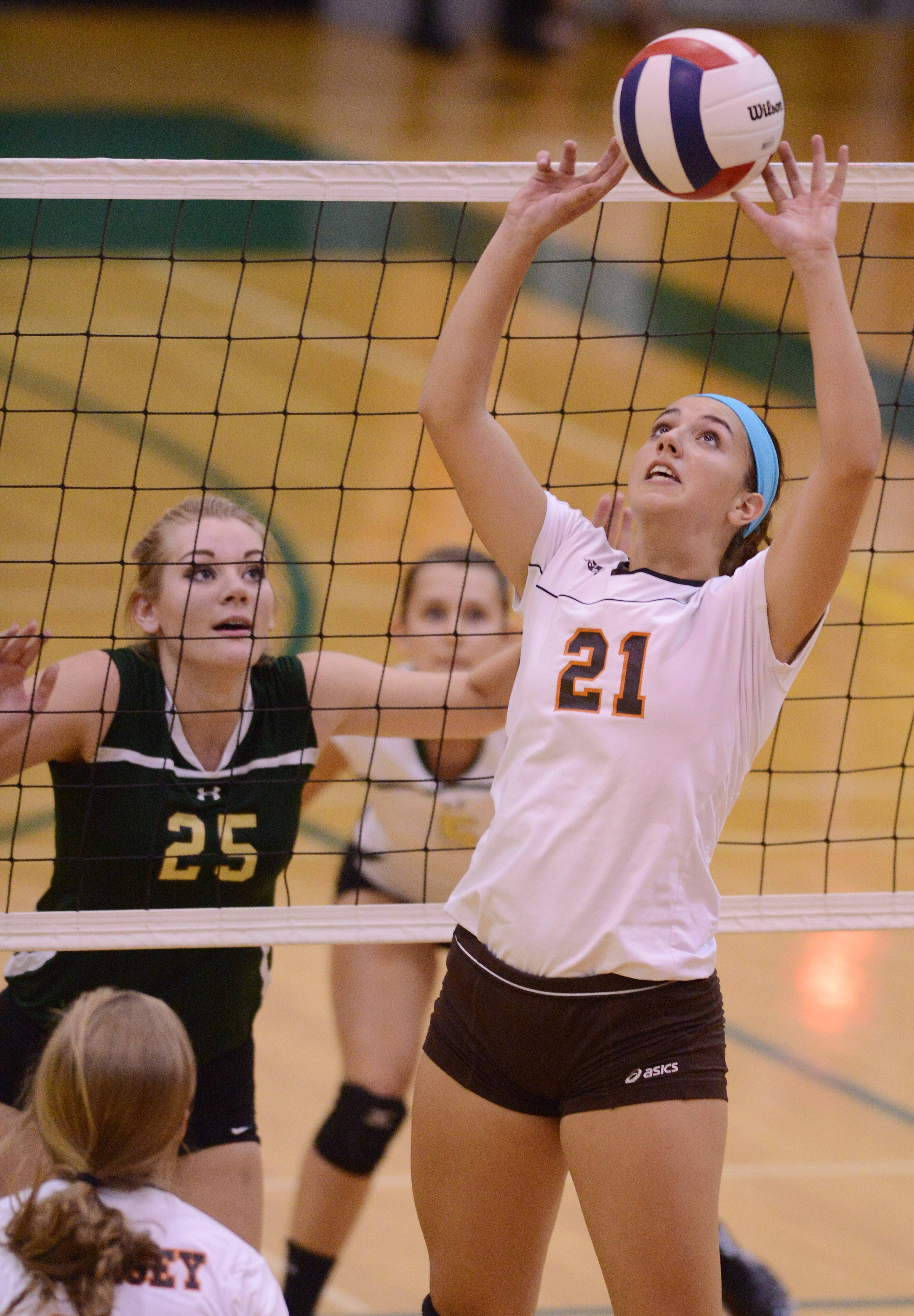 Hersey's Courtney Stedman, right, sets the ball at the net in front of Fremd's Lane Hindenburg during Tuesday's volleyball match in Palatine.