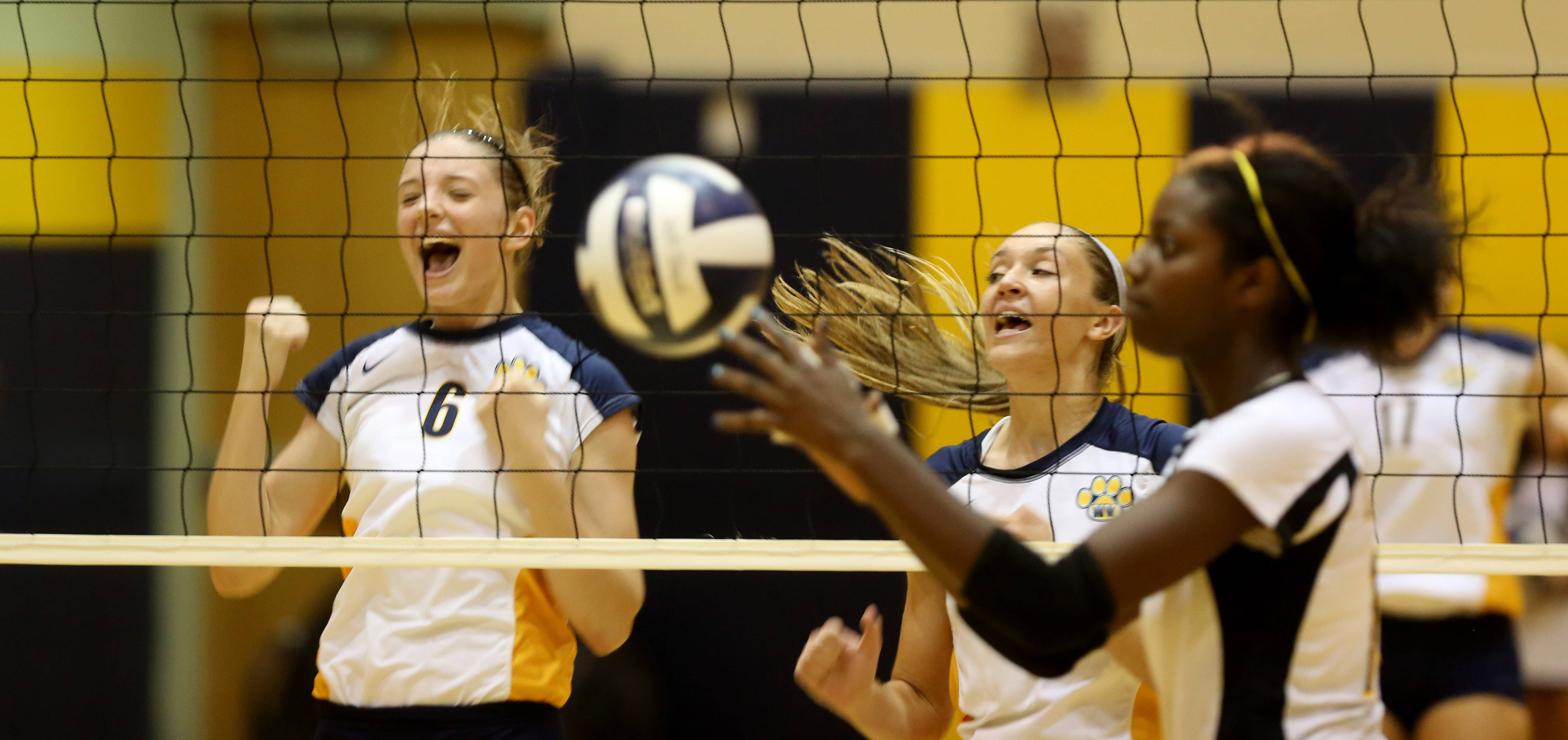 Neuqua Valley's Anne Botos (6) celebrates a point as Metea Valley's Ashley Walker gathers the ball, during girls volleyball action in Naperville.