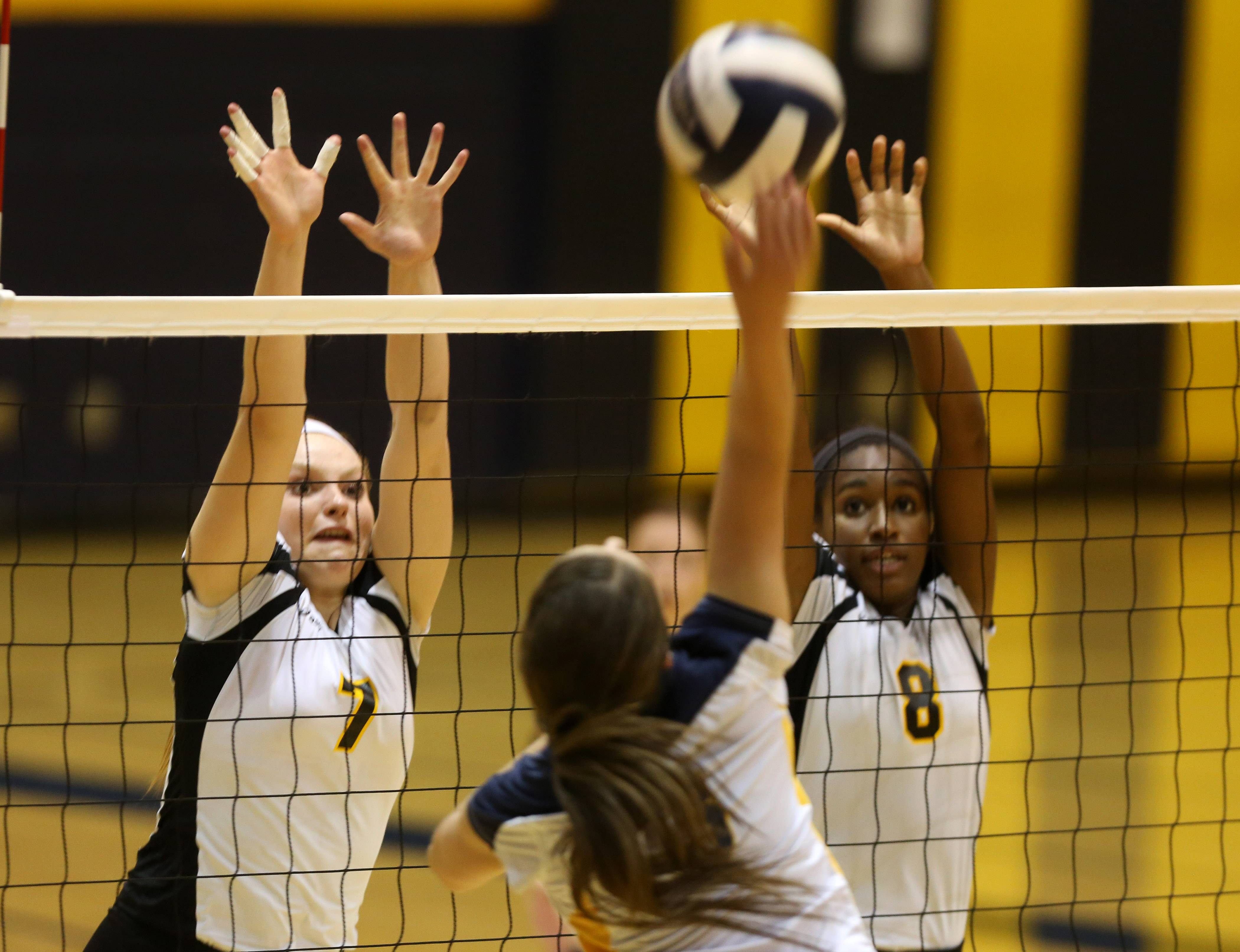 Metea Valley's Alexis Bass and Ashley Walker attempt to block a Neuqua Valley shot during girls volleyball action in Naperville.