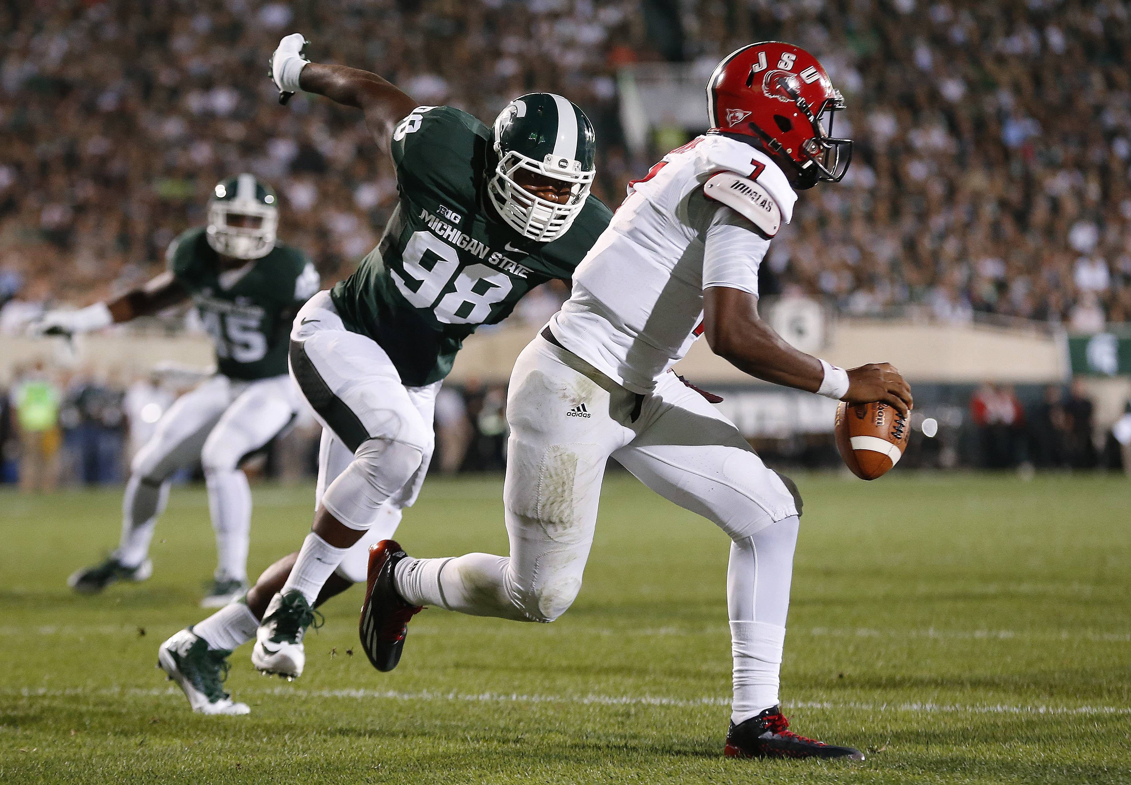 Michigan State defensive end Demetrius Cooper chases Jacksonville State quarterback Eli Jenkins Friday in East Lansing, Michigan. Michigan State visits Oregon Saturday in the first matchup of top 10 teams this season.