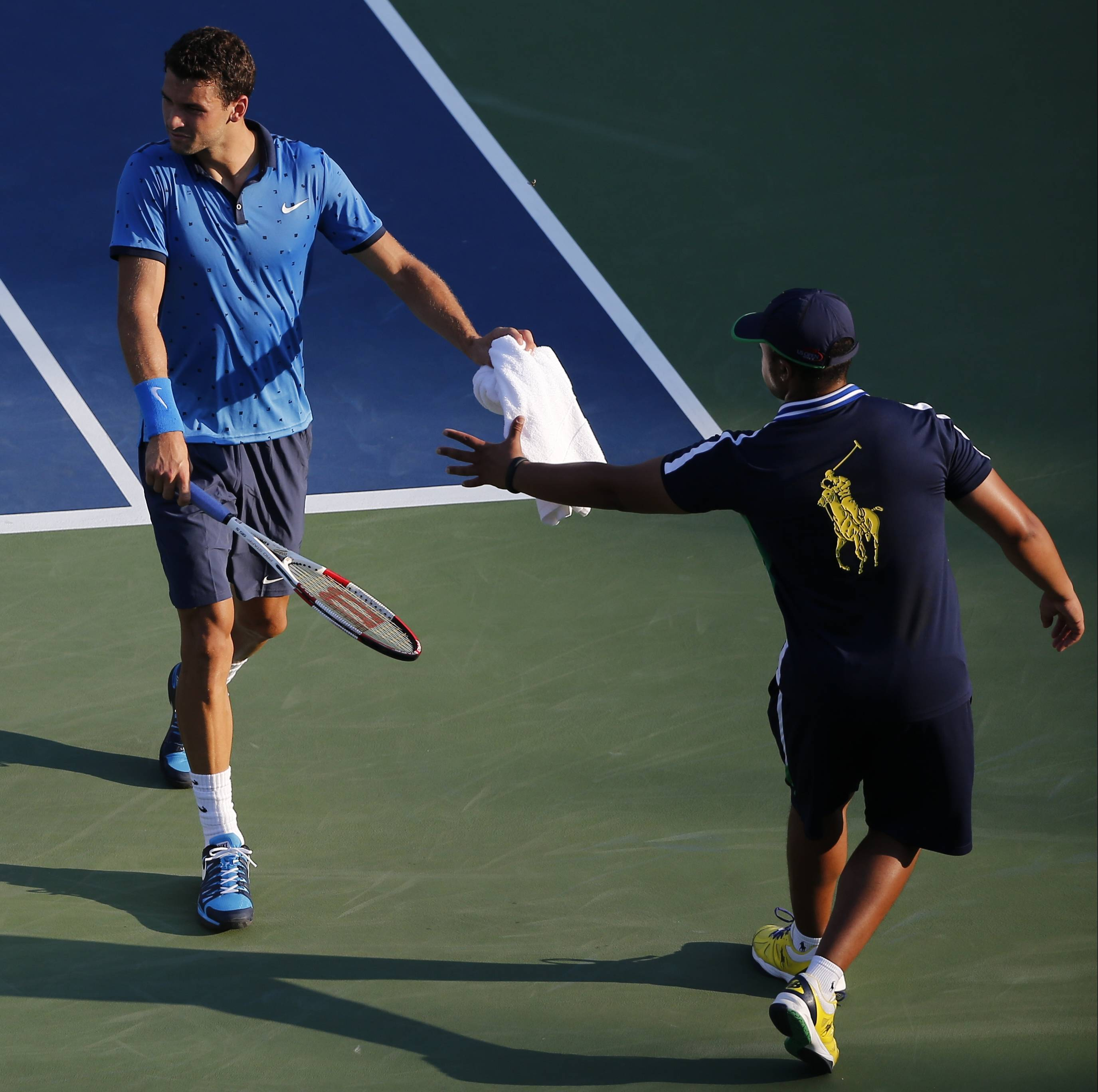Grigor Dimitrov, of Bulgaria, hands a towel back to a ball person after wiping sweat from his face during the second round of the 2014 U.S. Open tennis tournament, Wednesday, Aug. 27, 2014, in New York.