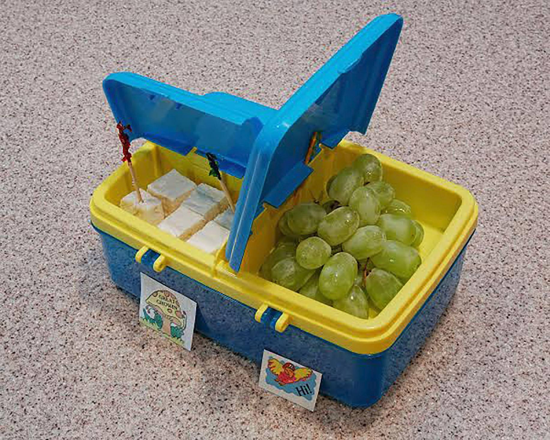 Courtesy of Christine PalumboA compartmentalized lunch box featuring cubed feta cheese and fresh grapes.