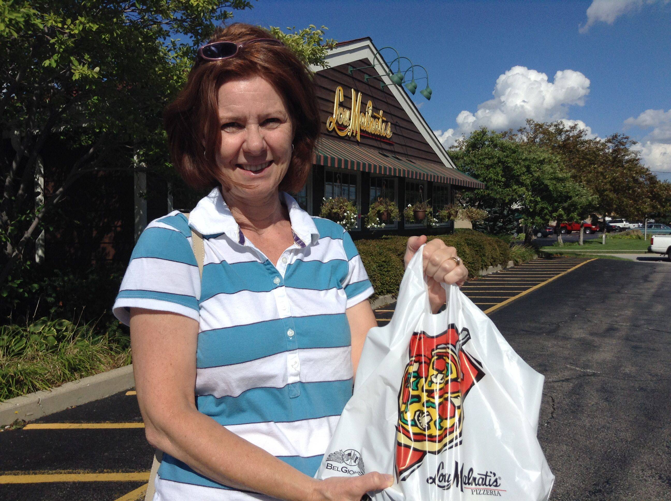 Surprised to see her favorite pizza place dissed by an East Coast pizza ranking, Hoffman Estates mom Laurie Sorman picks up a Lou Malnati's deep-dish cheese pizza for her daughter Bethany's 16th birthday on Wednesday.