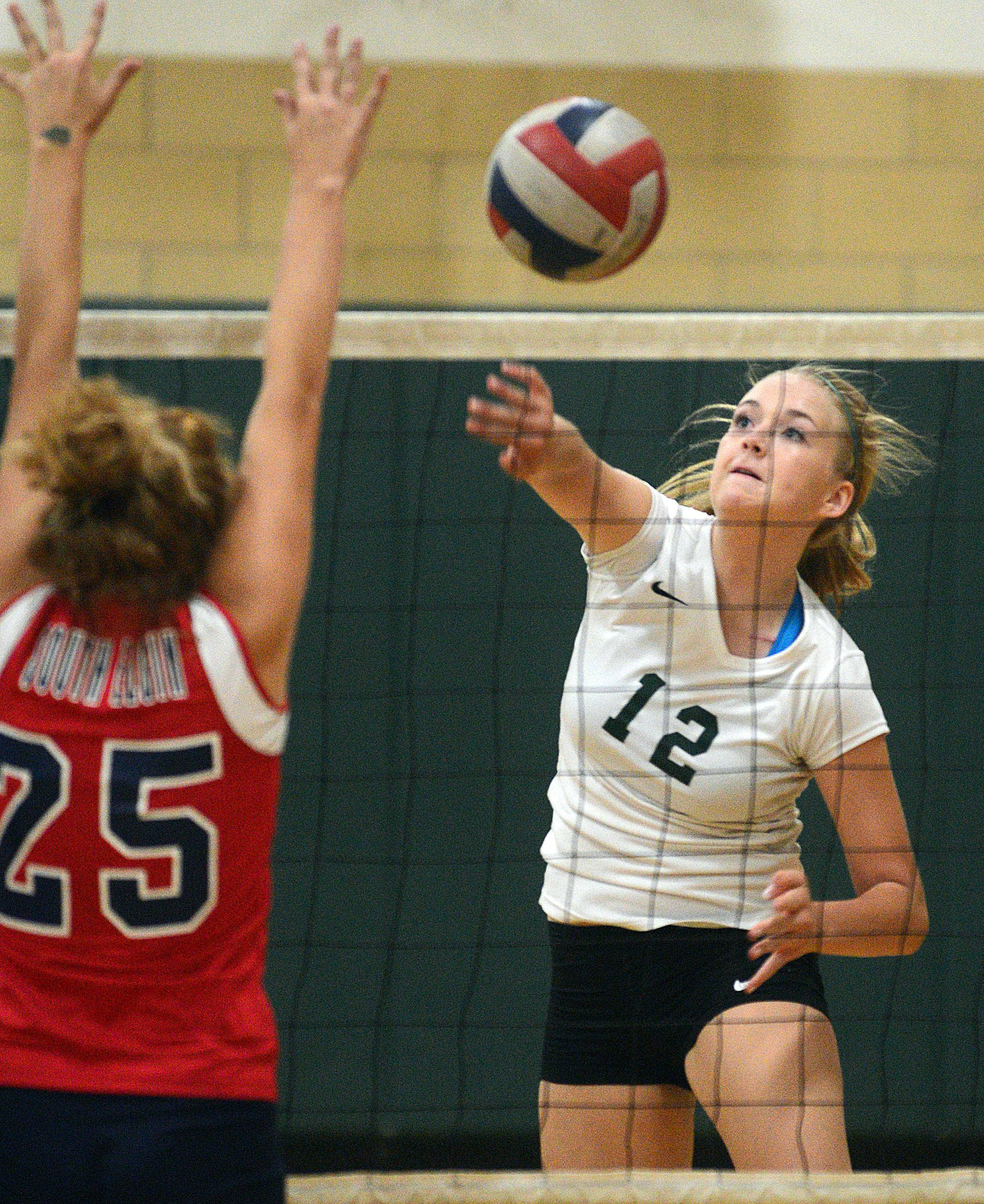 St. Edward's Cecile Rapp, right, hits the ball past South Elgin's Renee Rush during volleyball action at St. Edward on Wednesday evening.