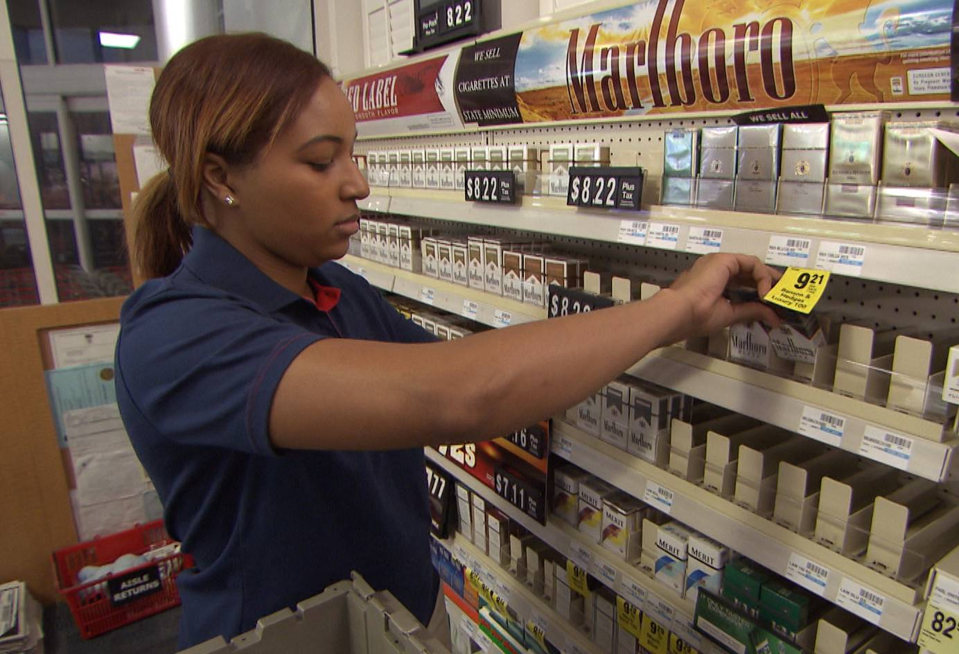 A CVS store employee removes tobacco products from the store shelves in East Greenwich, R.I.