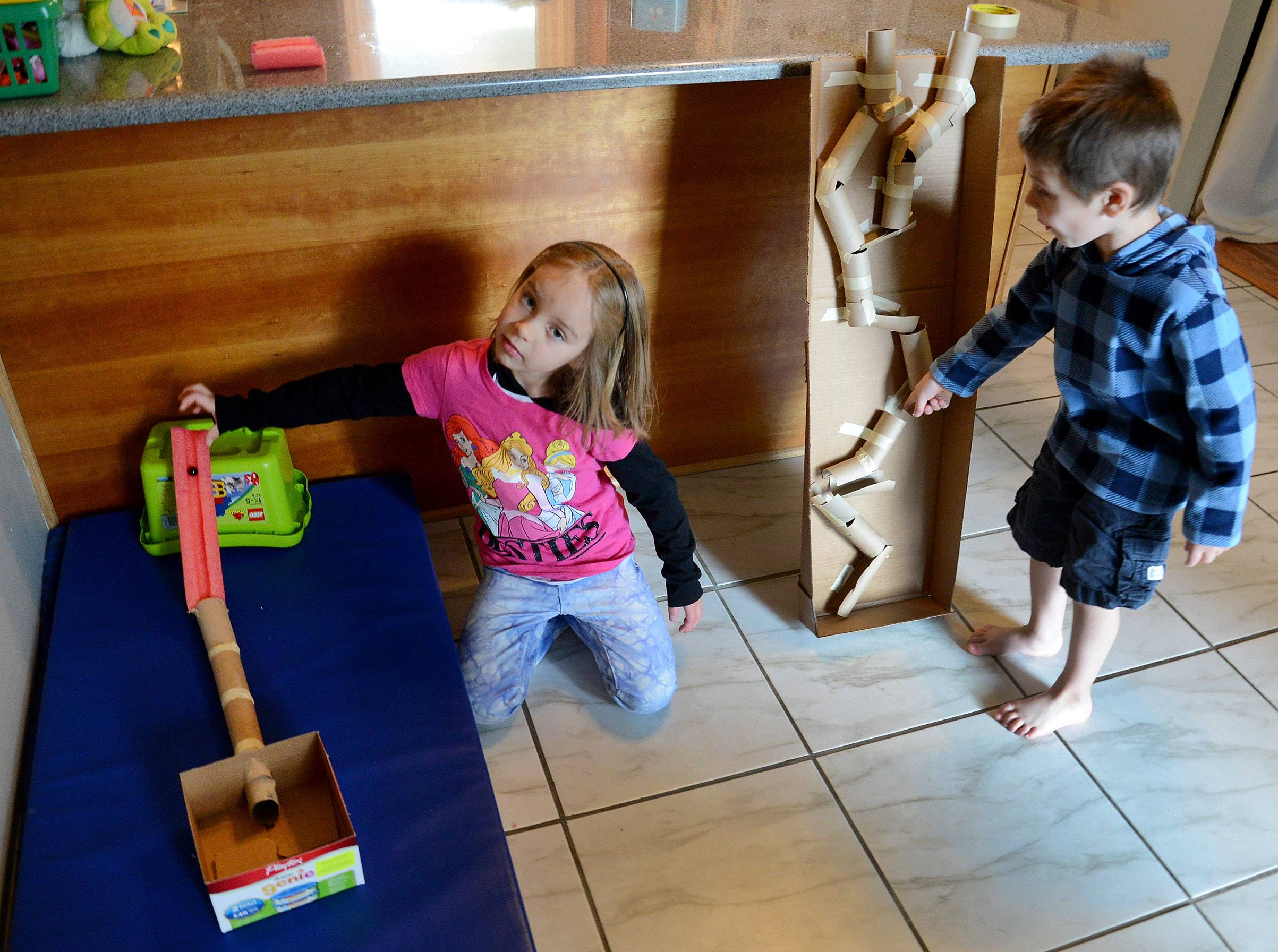 Lily and Justin Anderson demonstrate their marble runs in their kitchen.