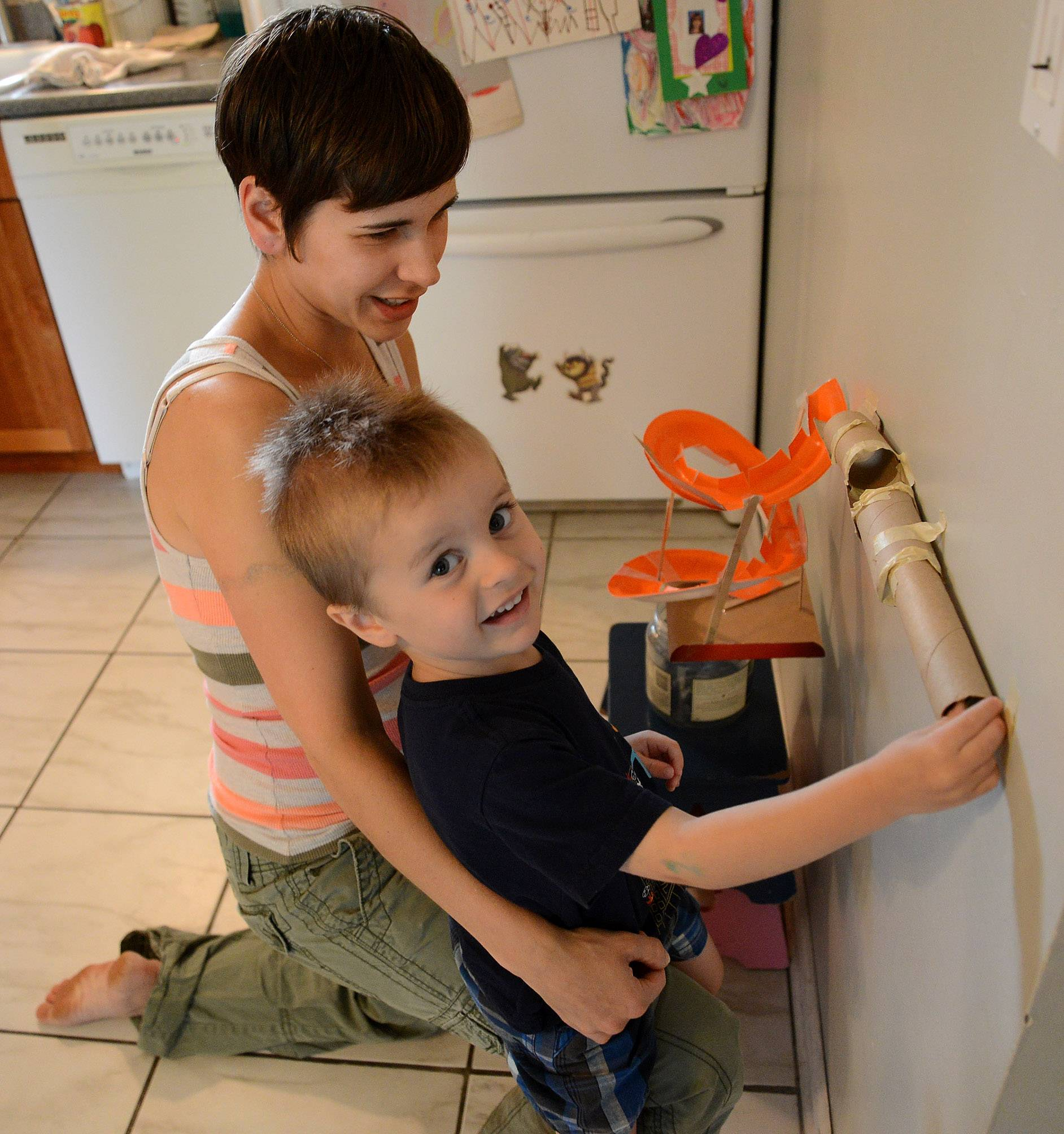 Benjamin Anderson and his mom demonstrate one of their marble runs they have set up in their kitchen.