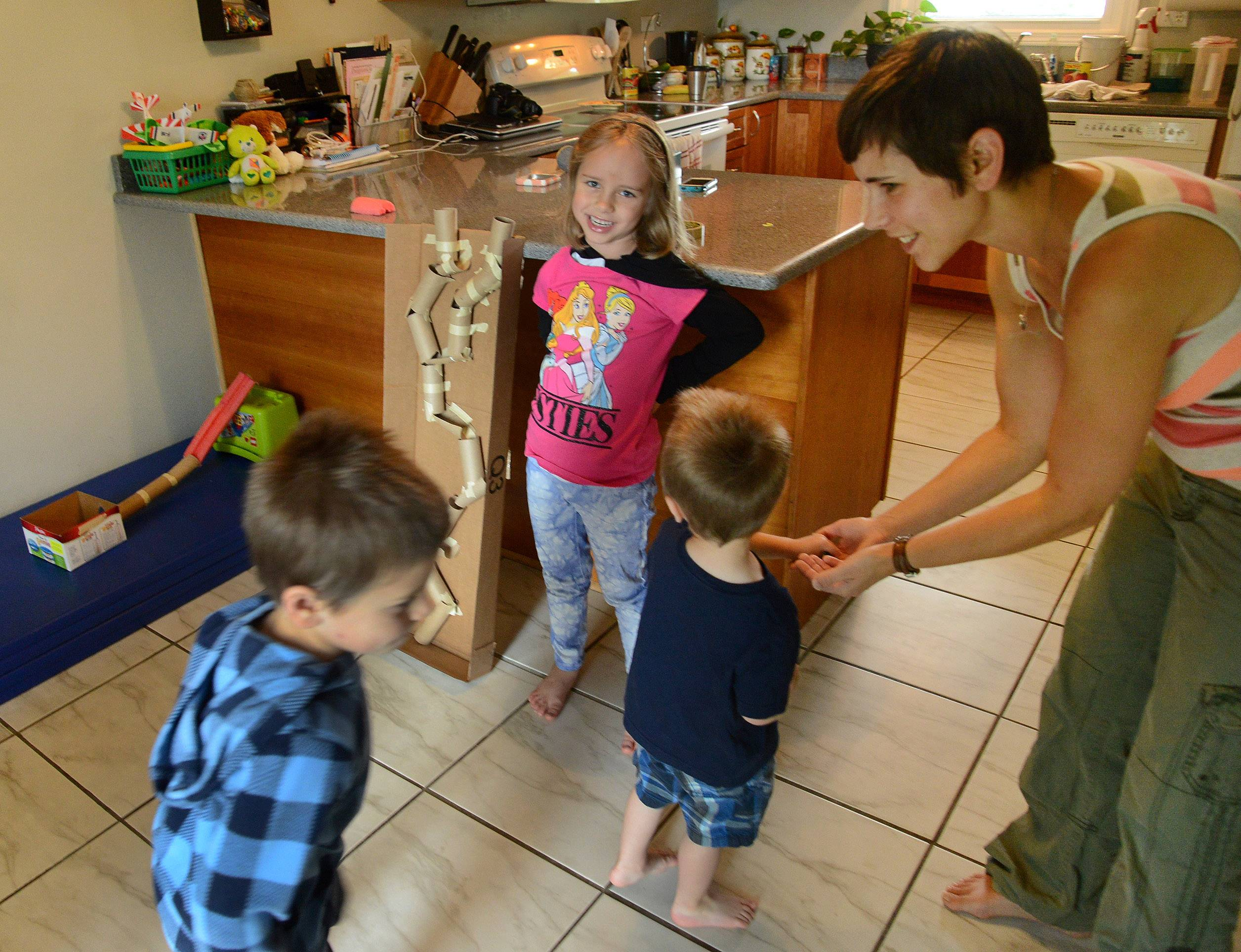 From left, Justin, 4, Lily, 6, Benjamin, 2, and mom Rebecca Anderson in their kitchen with their marble runs.