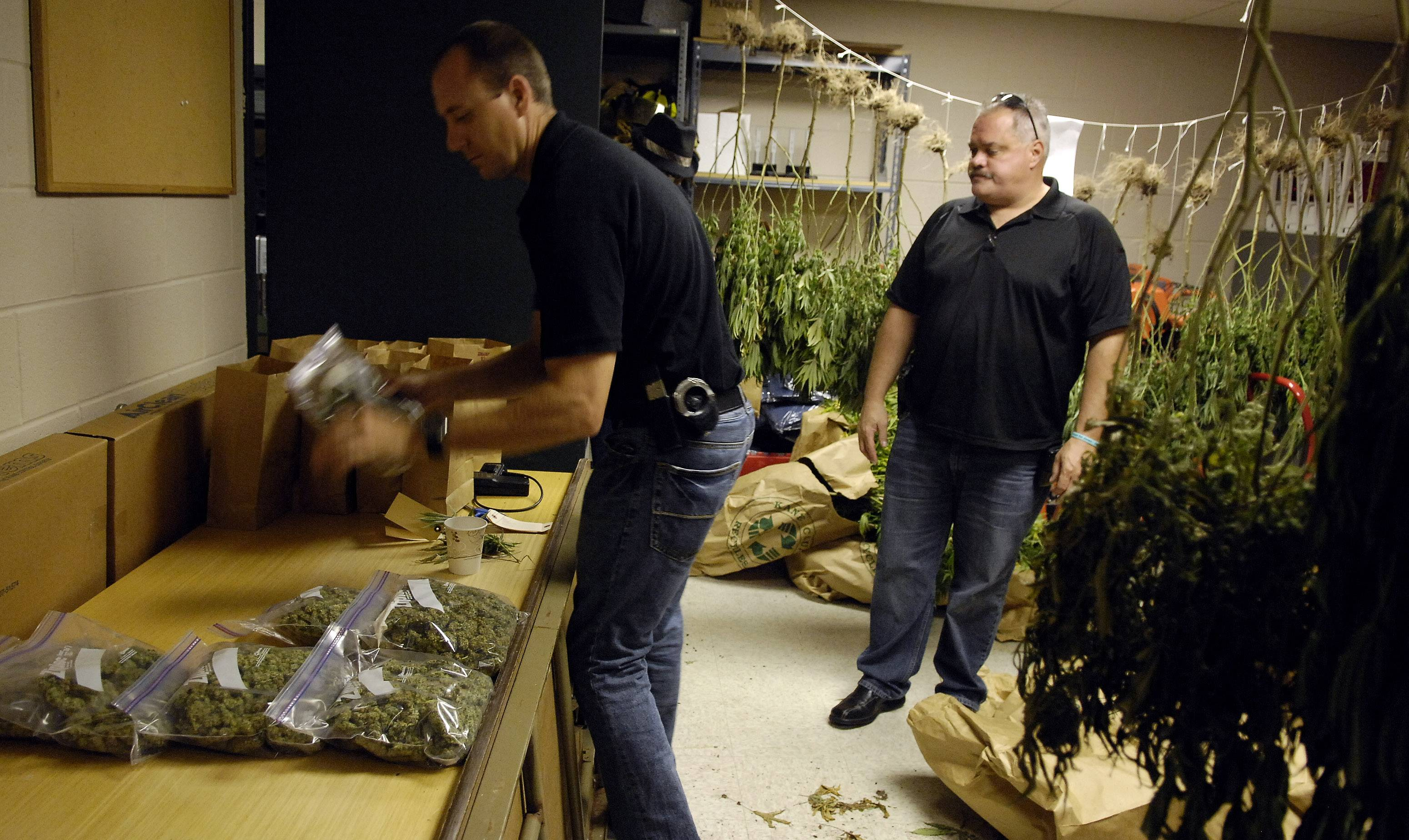 "Elgin Police Officer Jason A. Lentz, left, shows the spoils of a drug bust in 2008. Lentz was placed on leave last month after he allegedly posted on Facebook that a Missouri police officer ""did society a favor"" when he shot and killed unarmed teenager Michael Brown."