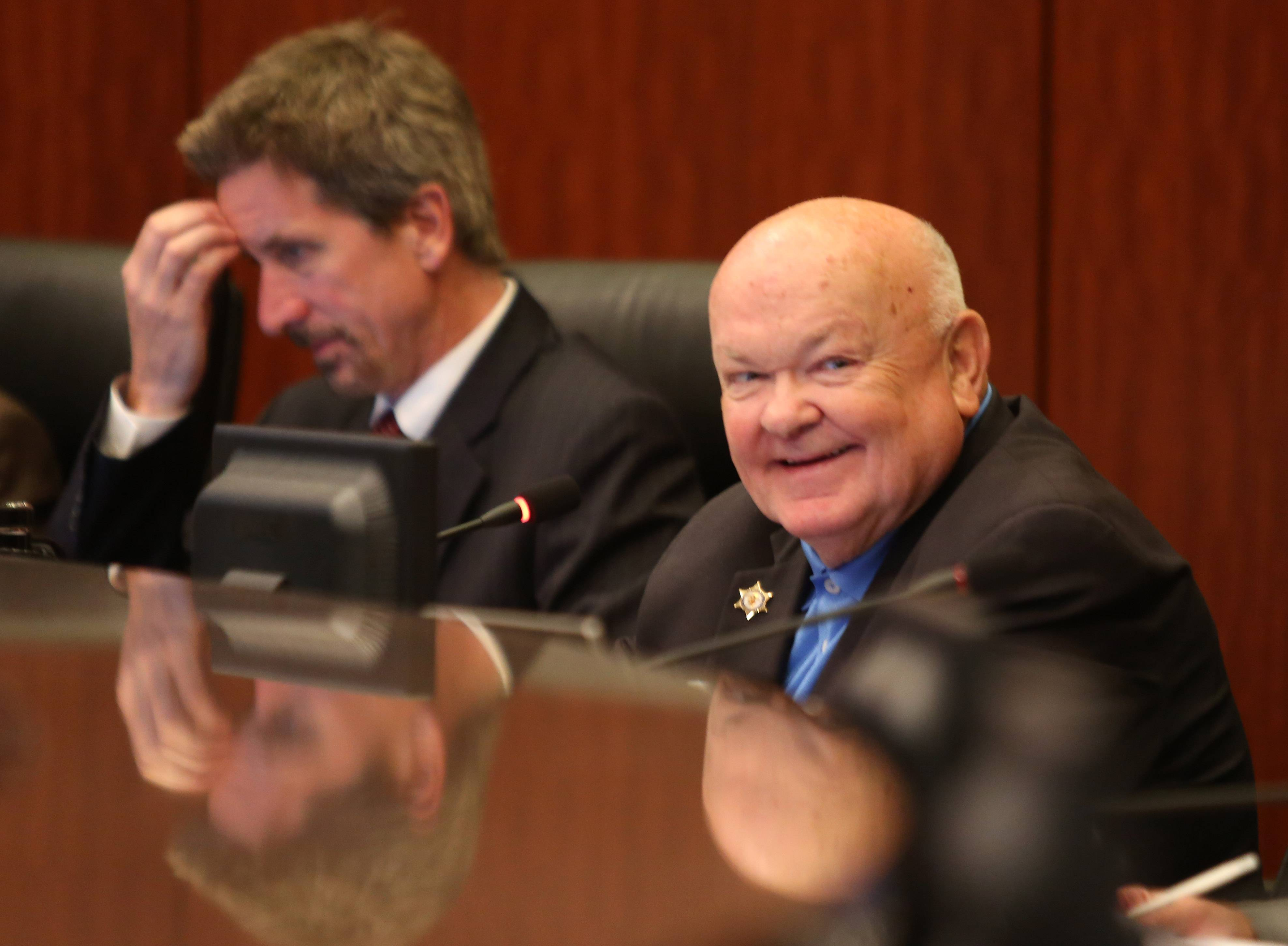 Naperville Mayor George Pradel, right, listens to a resident address the city council about proposed legislation limiting the sale of puppies from so-called puppy mills. At left is Douglas Krieger, city manager.