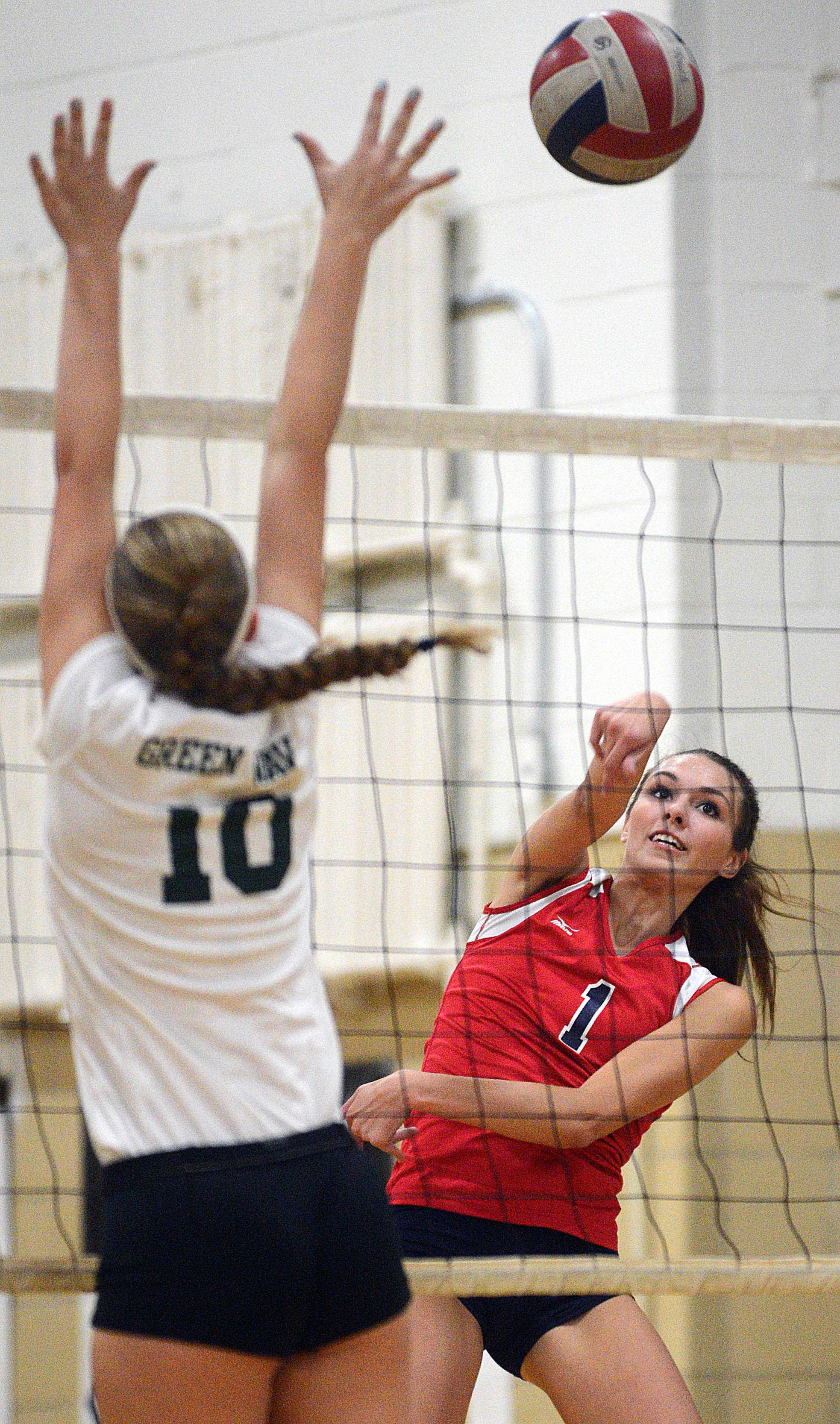 South Elgin's Katie Innis, right, hits the ball past St. Edward's Samantha Boydston during volleyball at St. Edward on Wednesday evening.