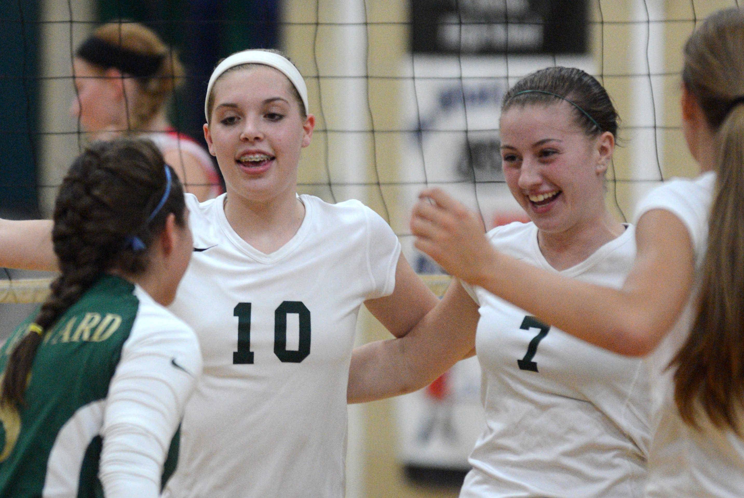 St. Edward Green Wave players come together during their game with South Elgin during volleyball at St. Edward on Wednesday evening. At left is Samantha Boydston and at right is Gabriella Tripicchio.