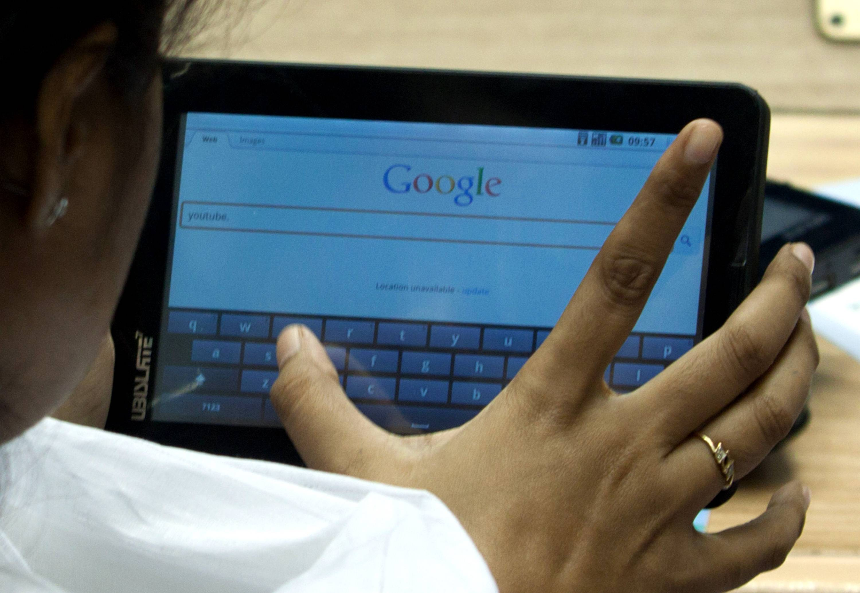 A student uses the 'Aakash' tablet computer to search the Google Web page during a news conference in New Delhi, India, on Wednesday, Oct. 5, 2011. India plans to sell tablet computers operating on Google Inc.'s Android system for students for as low as 1,100 rupees ($22) as Asia's third-biggest economy aims to boost usage of computers. Photographer: Pankaj Nangia/Bloomberg