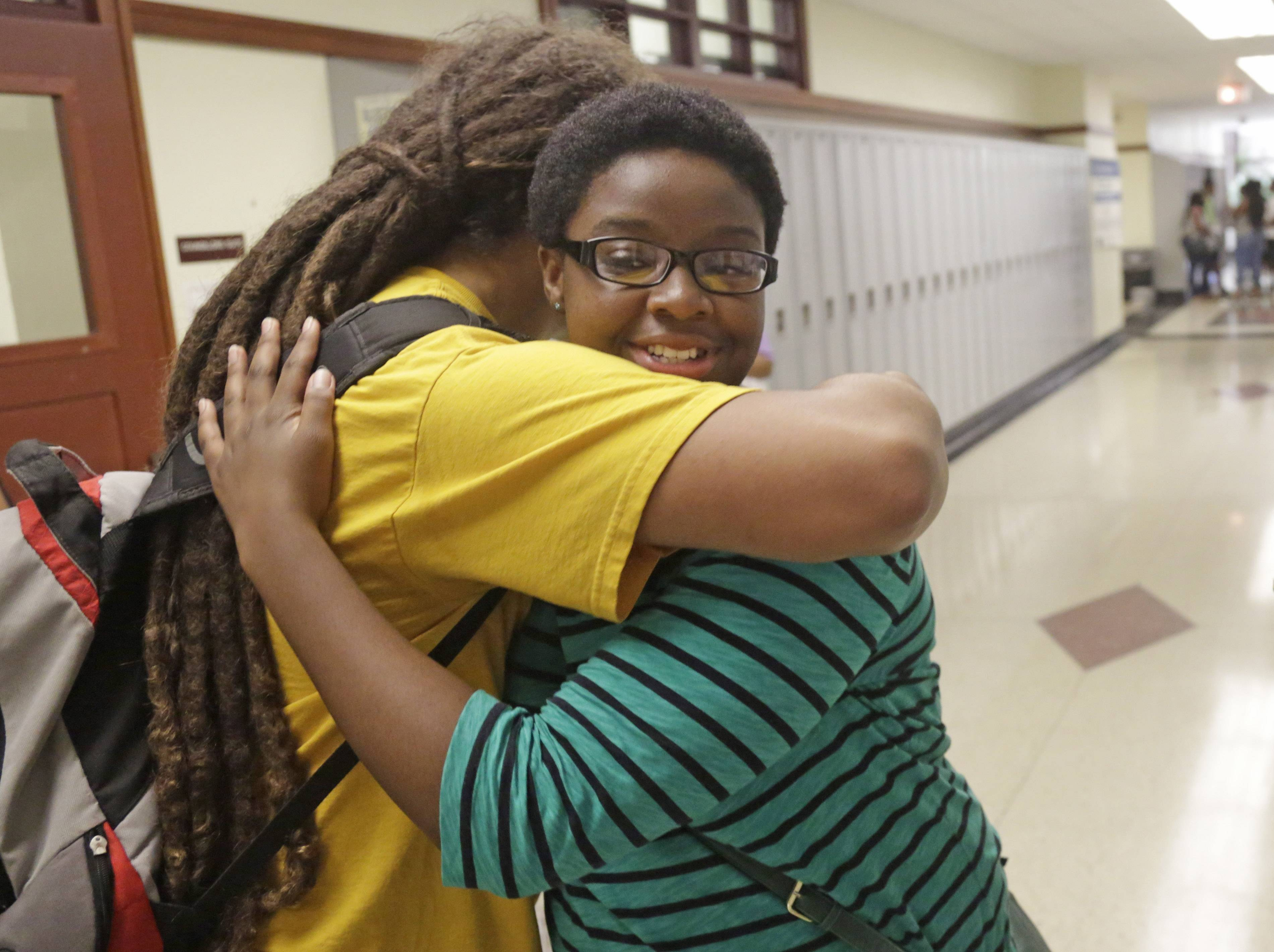 "Erin Nwachukwu, right, hugs her friend Yosef Smith during orientation day at Lindblom Math and Science Academy in Chicago. Nwachukwu, 16, says it's been difficult for her generation to keep the faith through multiple political scandals, a recession and various shootings — including the recent shooting of a young man in Ferguson, Missouri. ""We need more people who are setting a good example,"" she says."