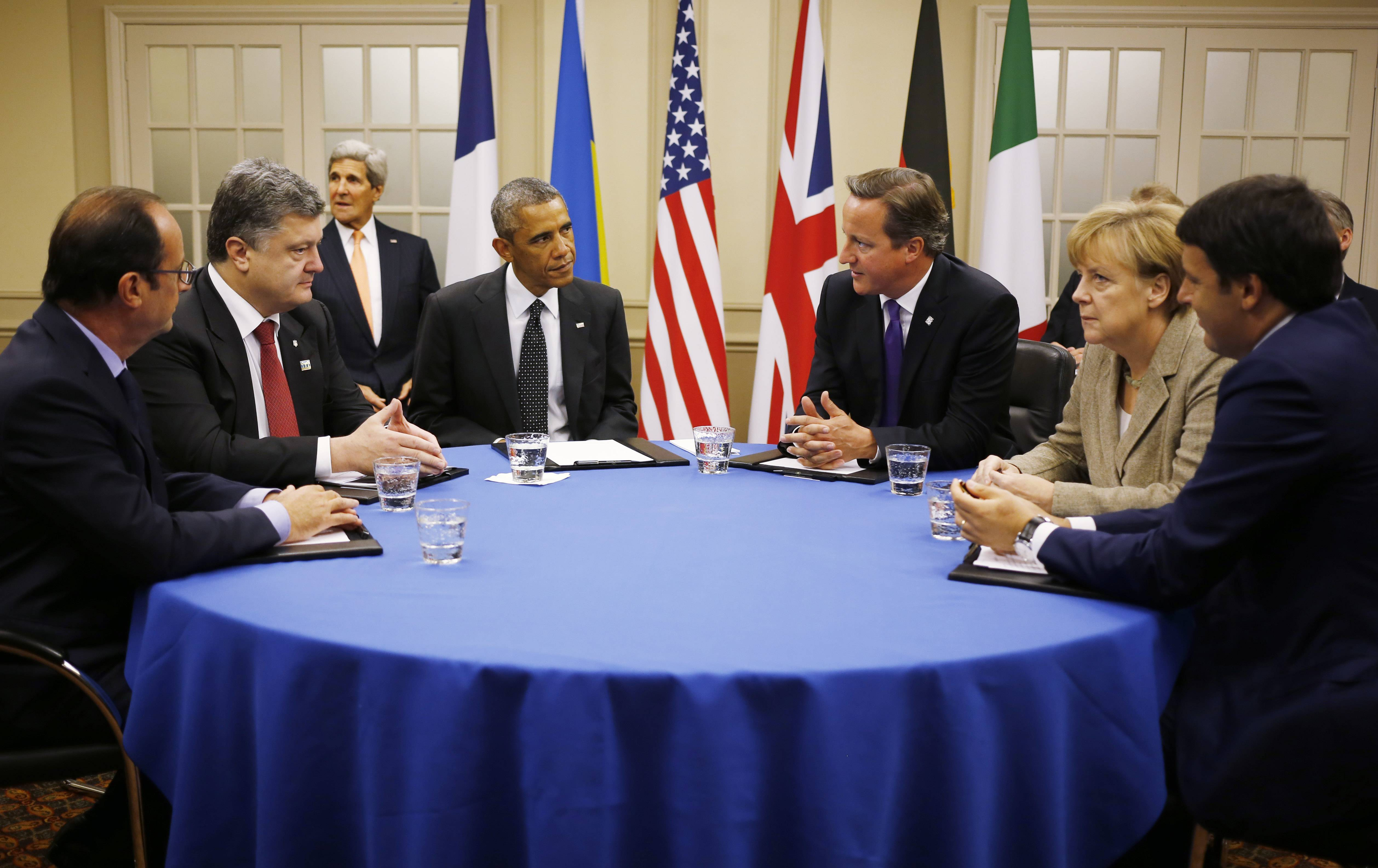 President Barack Obama, fourth from left, is seated at a table with, from left to right: France's President Francois Hollande, Ukraine President Petro Poroshenko, British Prime Minister David Cameron, German Chancellor Angela Merkel and Italian Prime Minister Matteo Renzi, as they discuss Ukraine at the NATO summit in Newport, Wales, Thursday. U.S. Secretary of State John Kerry is seated at rear left.