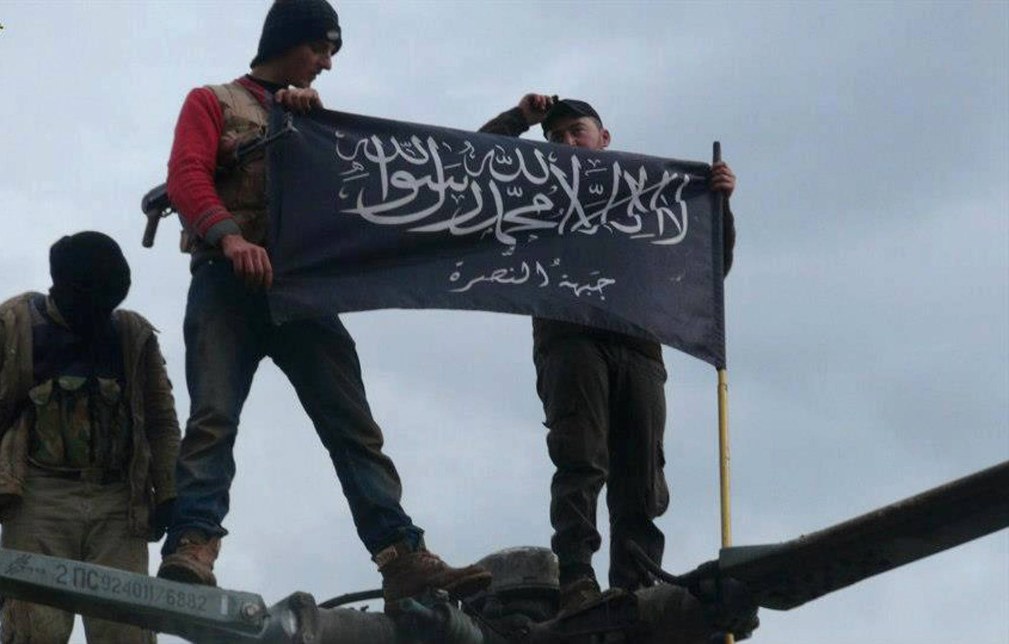 Rebels from al-Qaida affiliated Jabhat al-Nusra, also known as the Nusra Front, wave its brigade flag as they step on the top of a Syrian air force helicopter at Taftanaz air base in Idlib province, northern Syria.