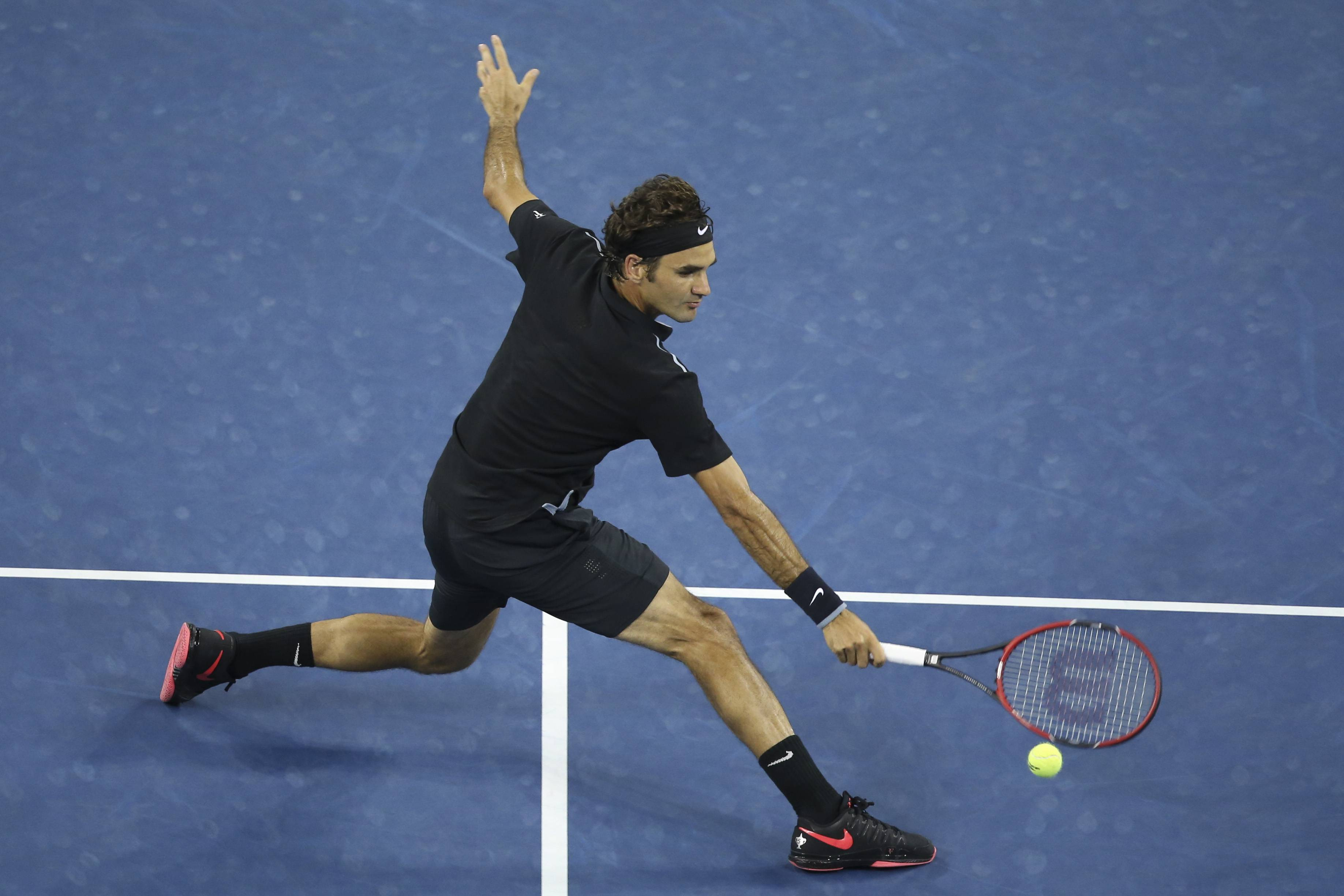 Roger Federer, of Switzerland, hits a backhand to Gael Monfils, of France, during the quarterfinals of the U.S. Open tennis tournament, Thursday, Sept. 4, 2014, in New York. (AP Photo/John Minchillo)