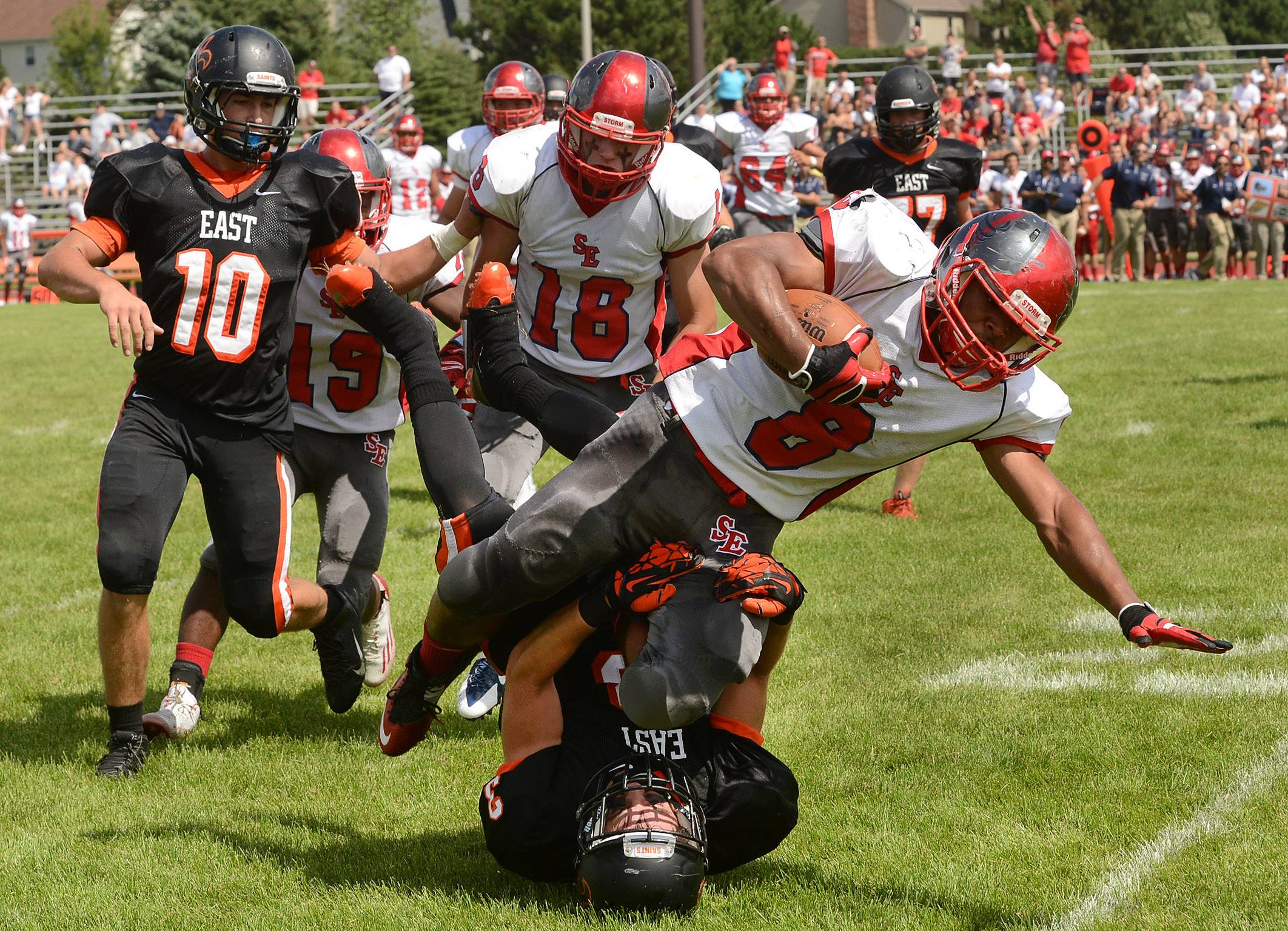 Kyle Ware of South Elgin crashes over Tommy Fink of St. Charles East during Week 1 action.