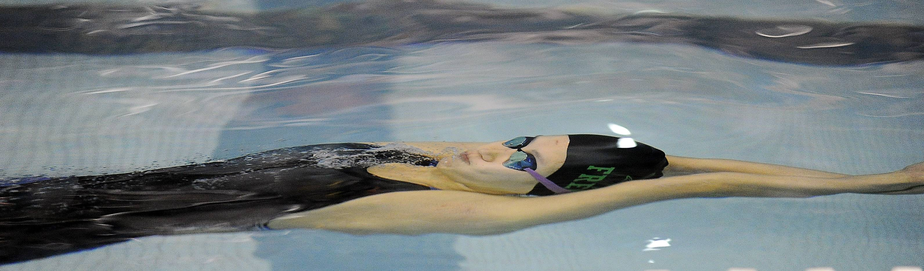 Fremd's Saki Takumiya extends her backstroke start underwater during last year's state meet prelims at New Trier.